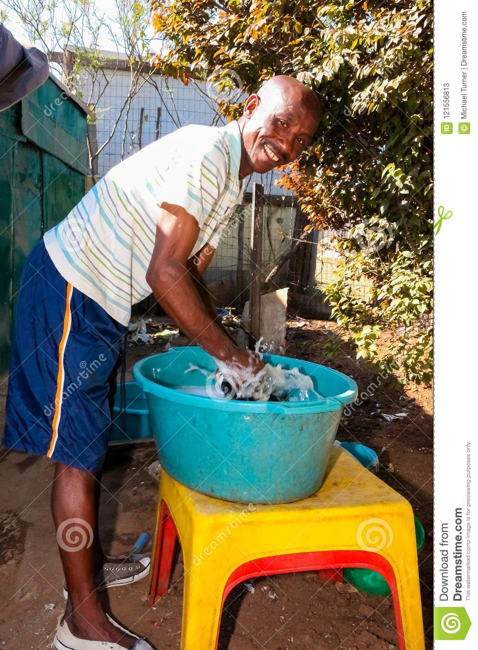 Teacher Washing Clothes At Creche Daycare In Suburban Soweto