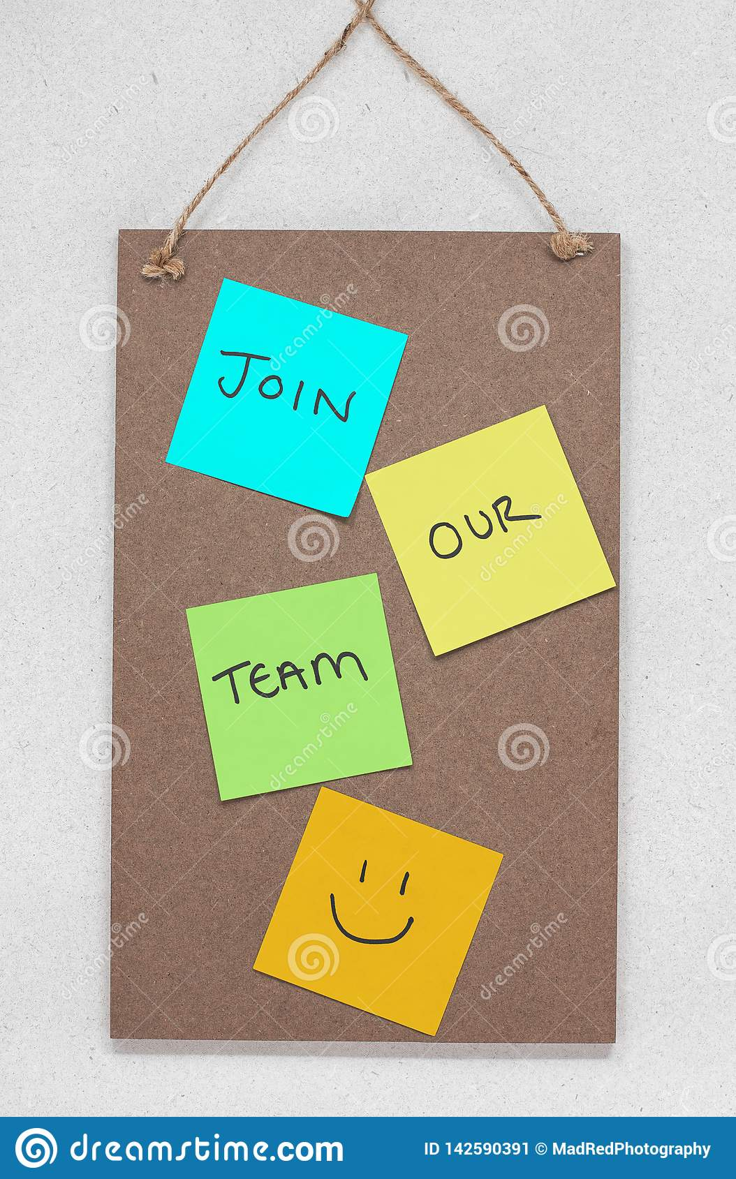 Join our team, text written on colourful sticky notes on a wooden noticeboard