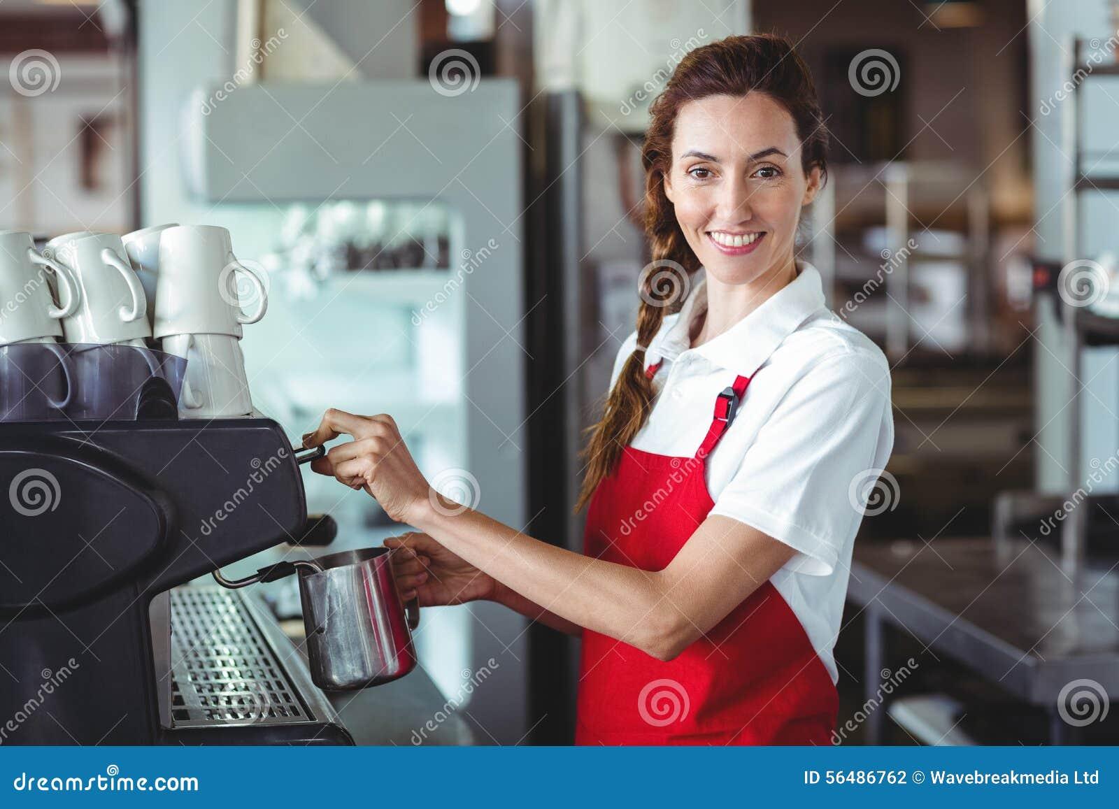 Joli barman regardant l appareil-photo et à l aide de la machine de café