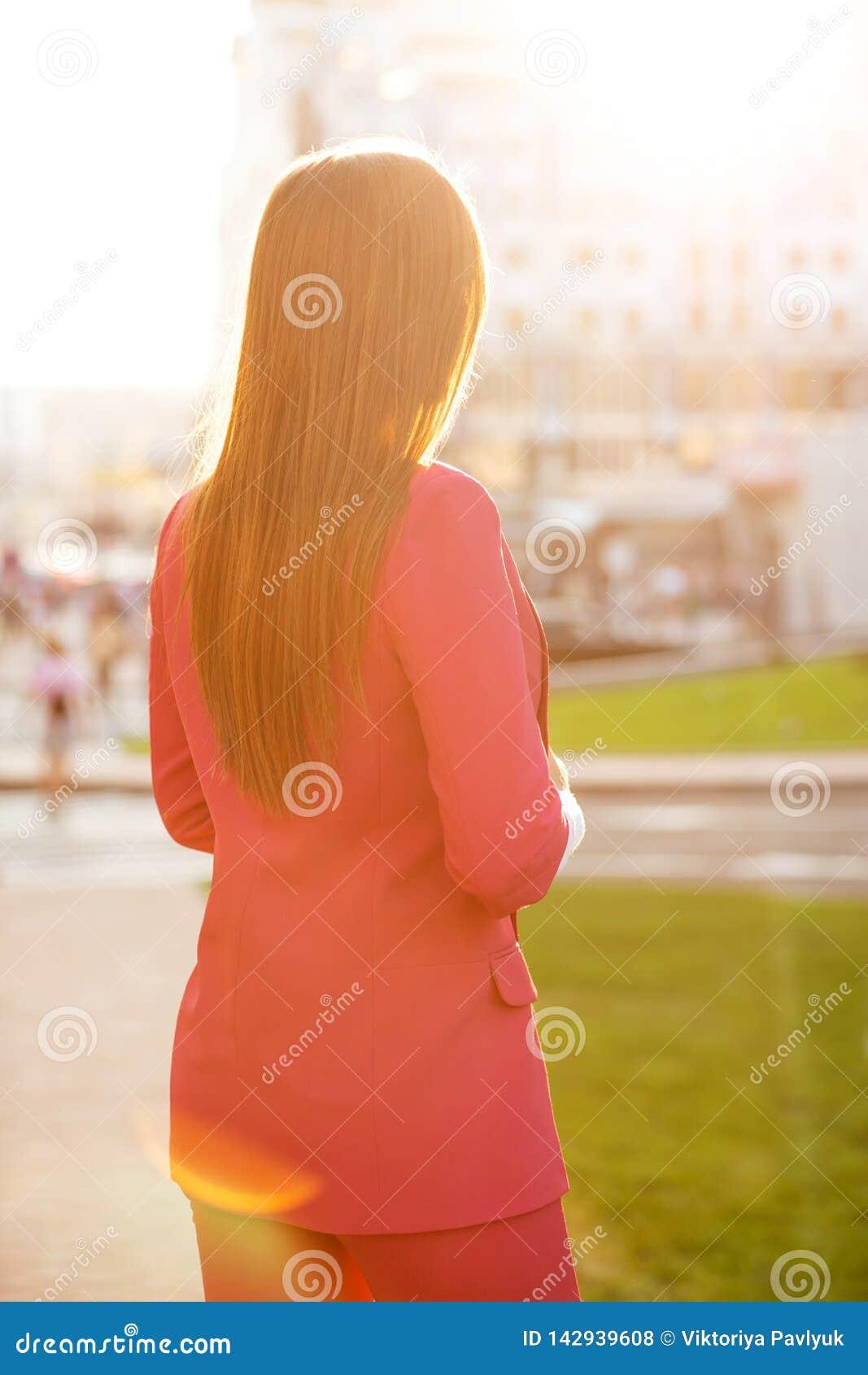 Joli modèle de brune dans le costume rose regardant les bâtiments de ville avec la lumière molle du soleil Vue arrière