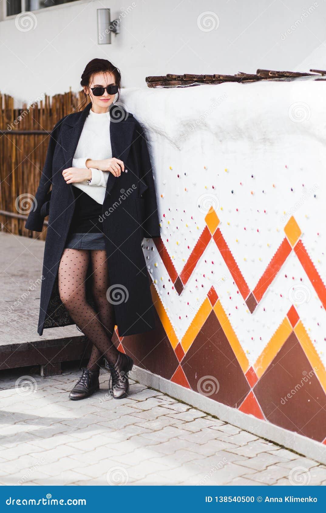 Joli modèle de femme de mode utilisant un manteau foncé et un chandail blanc, dans des lunettes de soleil, posant au-dessus du fo