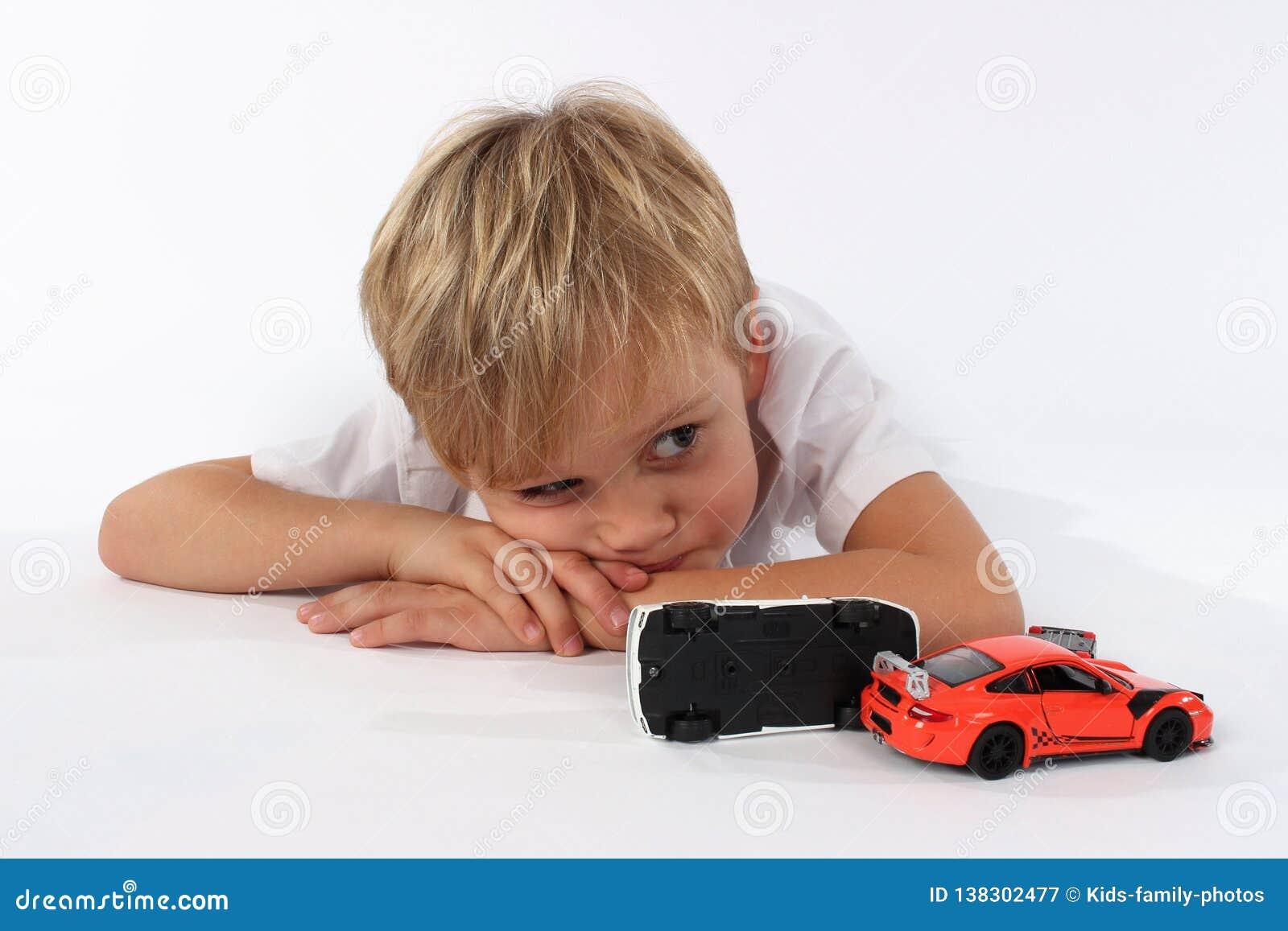 Joli petit garçon se trouvant derrière les jouets brisés de voiture et semblant ennuyé ou fatigué