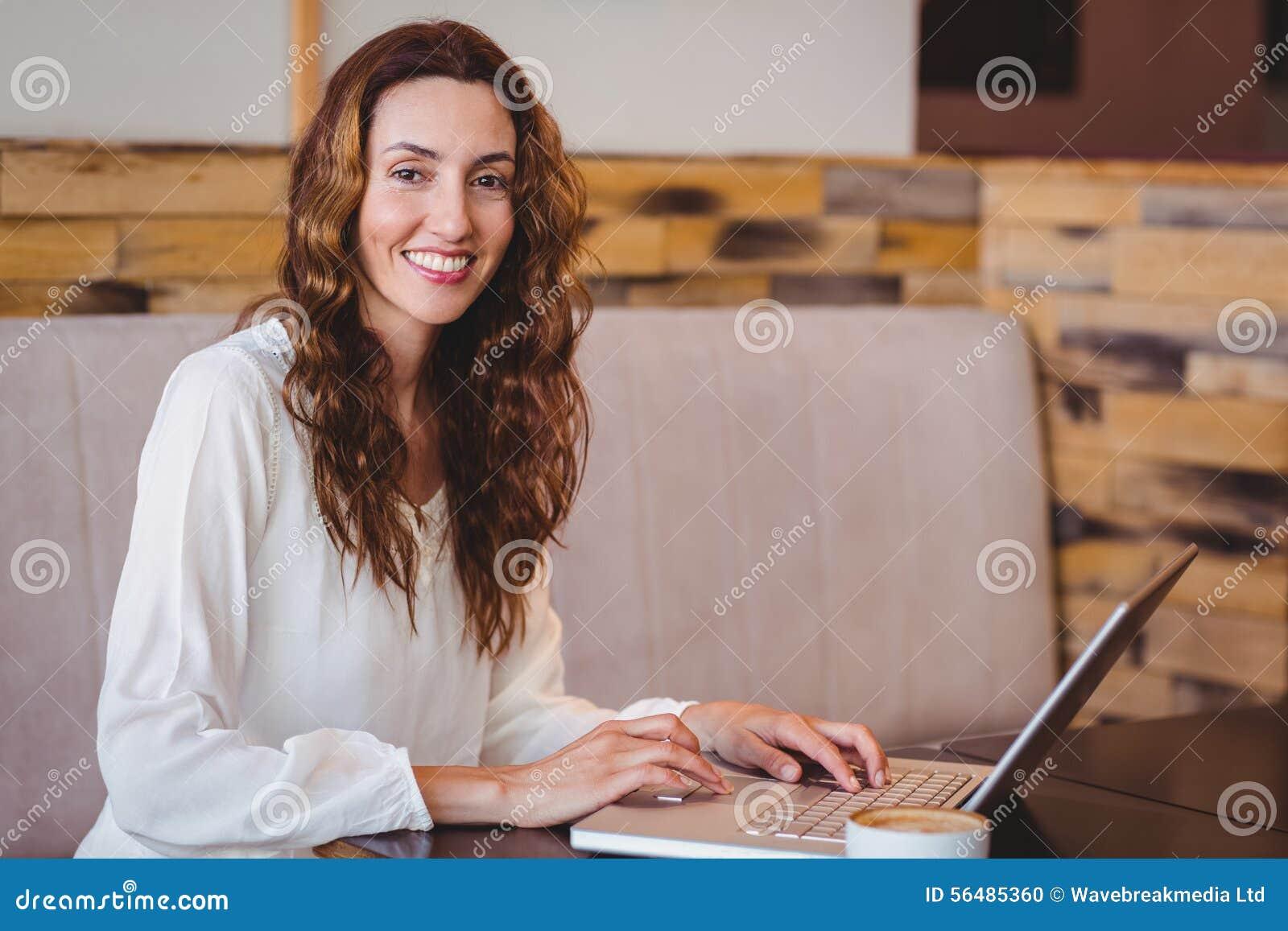 Jolie brune ayant le café utilisant l ordinateur portable