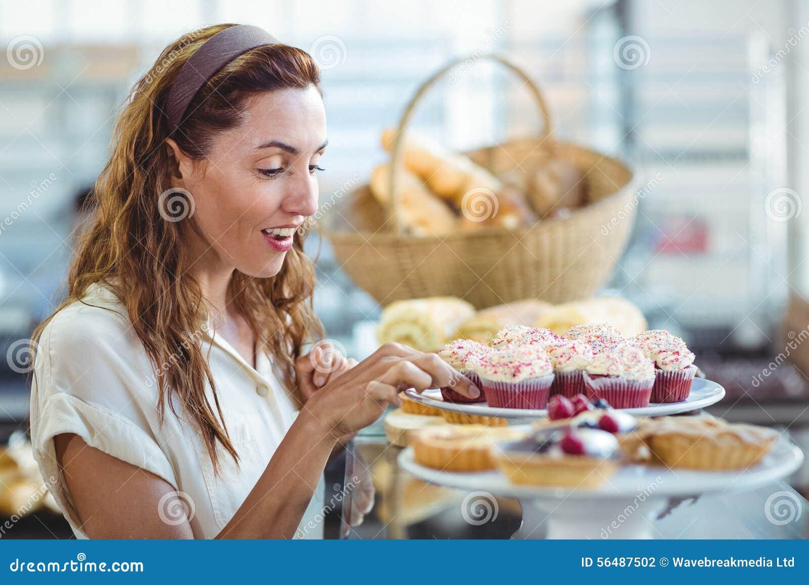 Jolie brune choisissant le petit gâteau