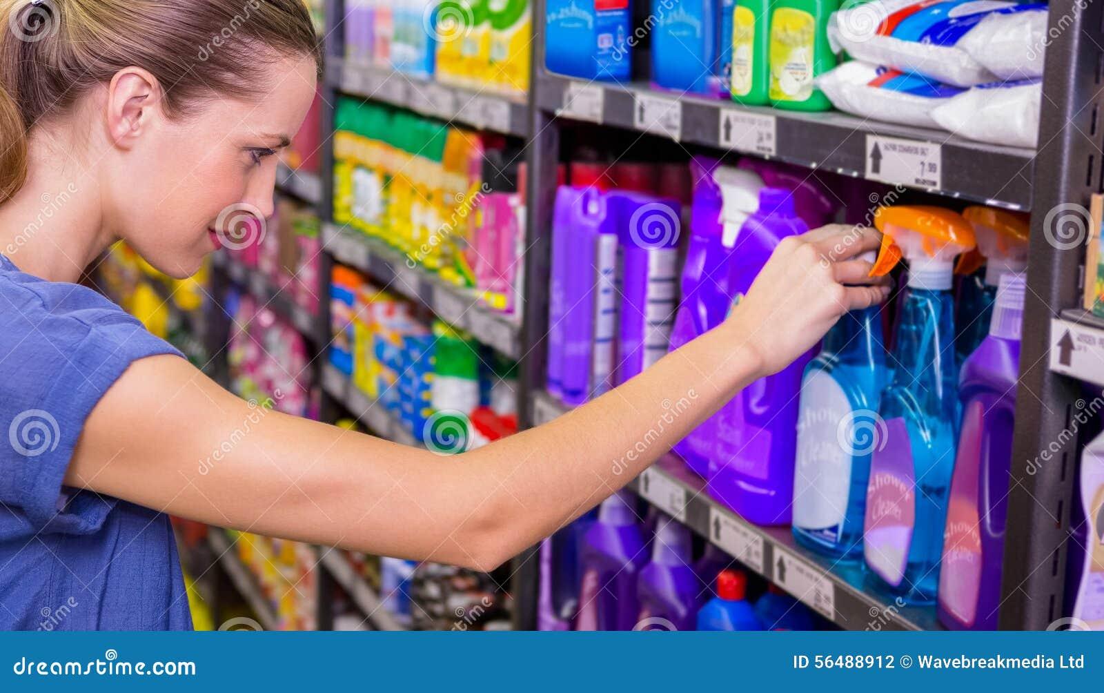 Jolie brune réfléchie regardant le produit dans l étagère