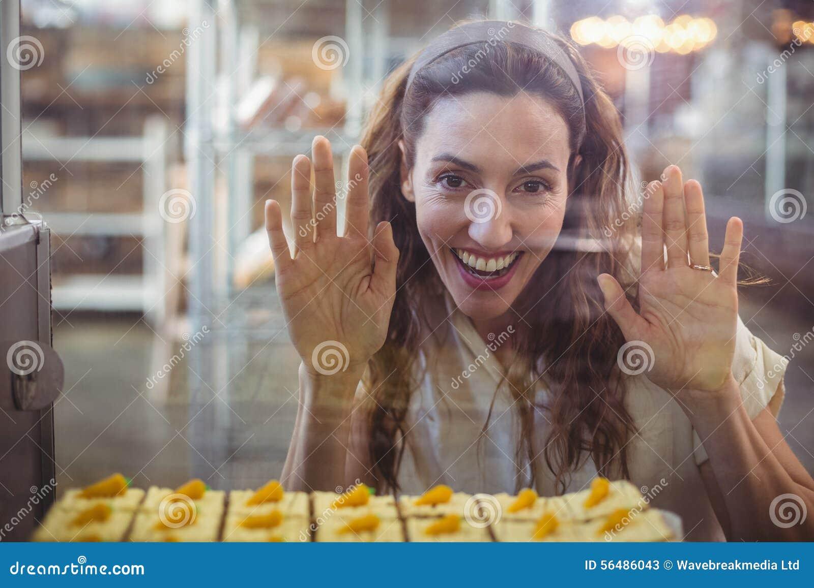 Jolie brune regardant des pâtisseries par le verre