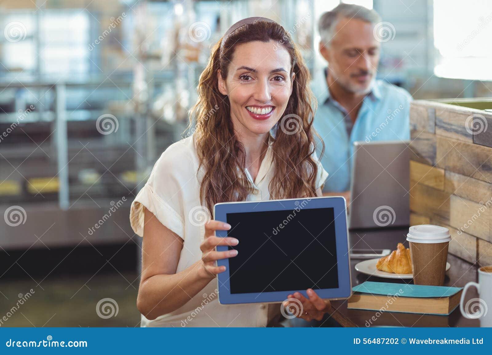 Jolie brune regardant l appareil-photo et montrant le comprimé