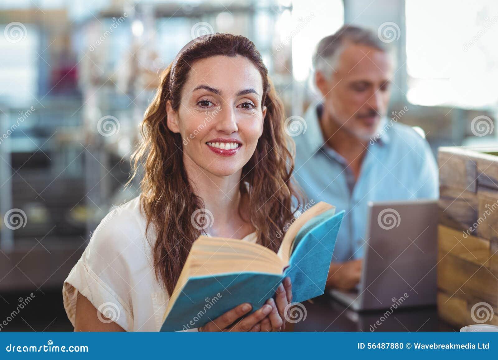 Jolie brune regardant l appareil-photo et tenant le livre