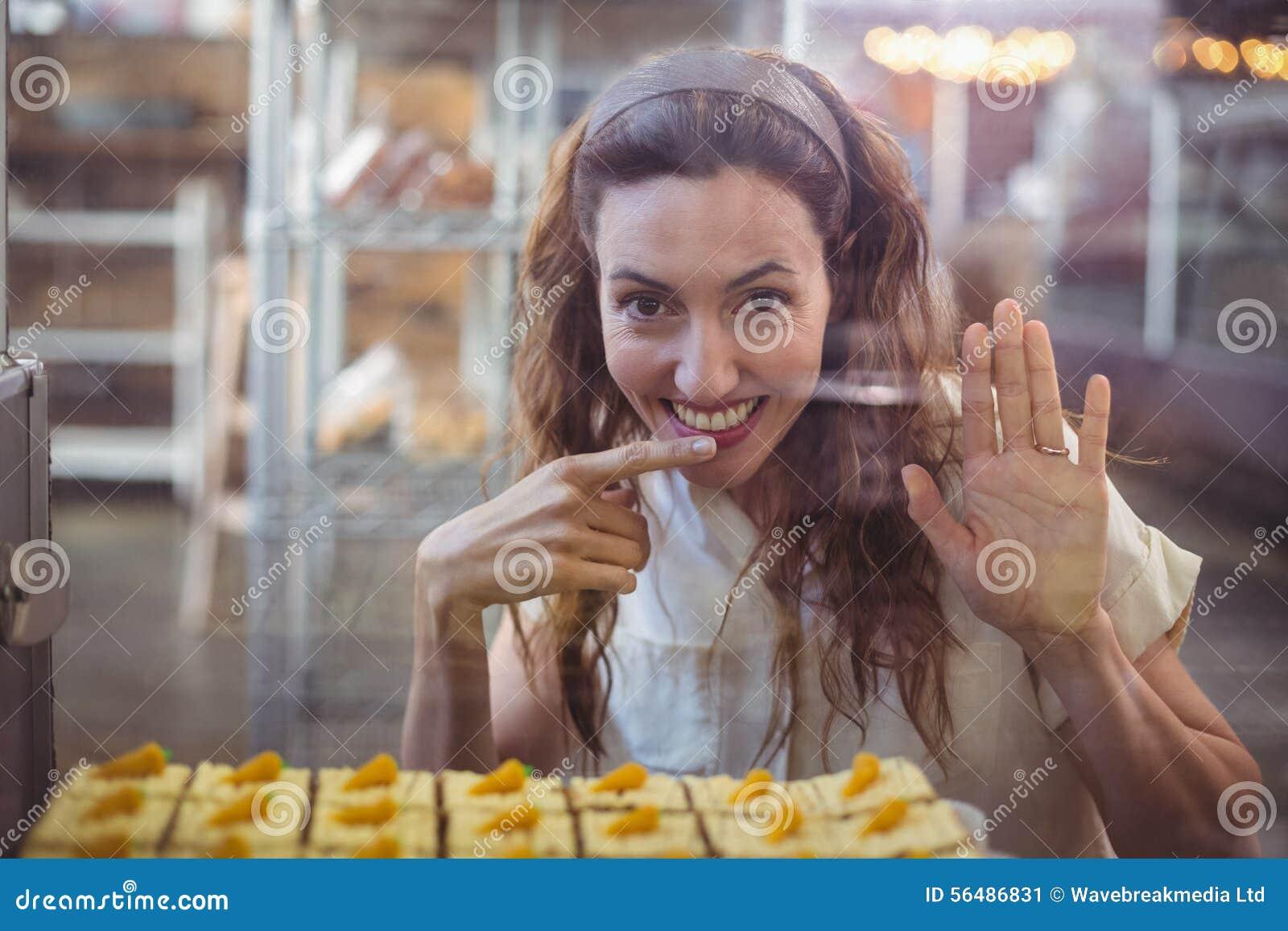 Jolie brune regardant l appareil-photo par le verre avec le doigt dans la bouche