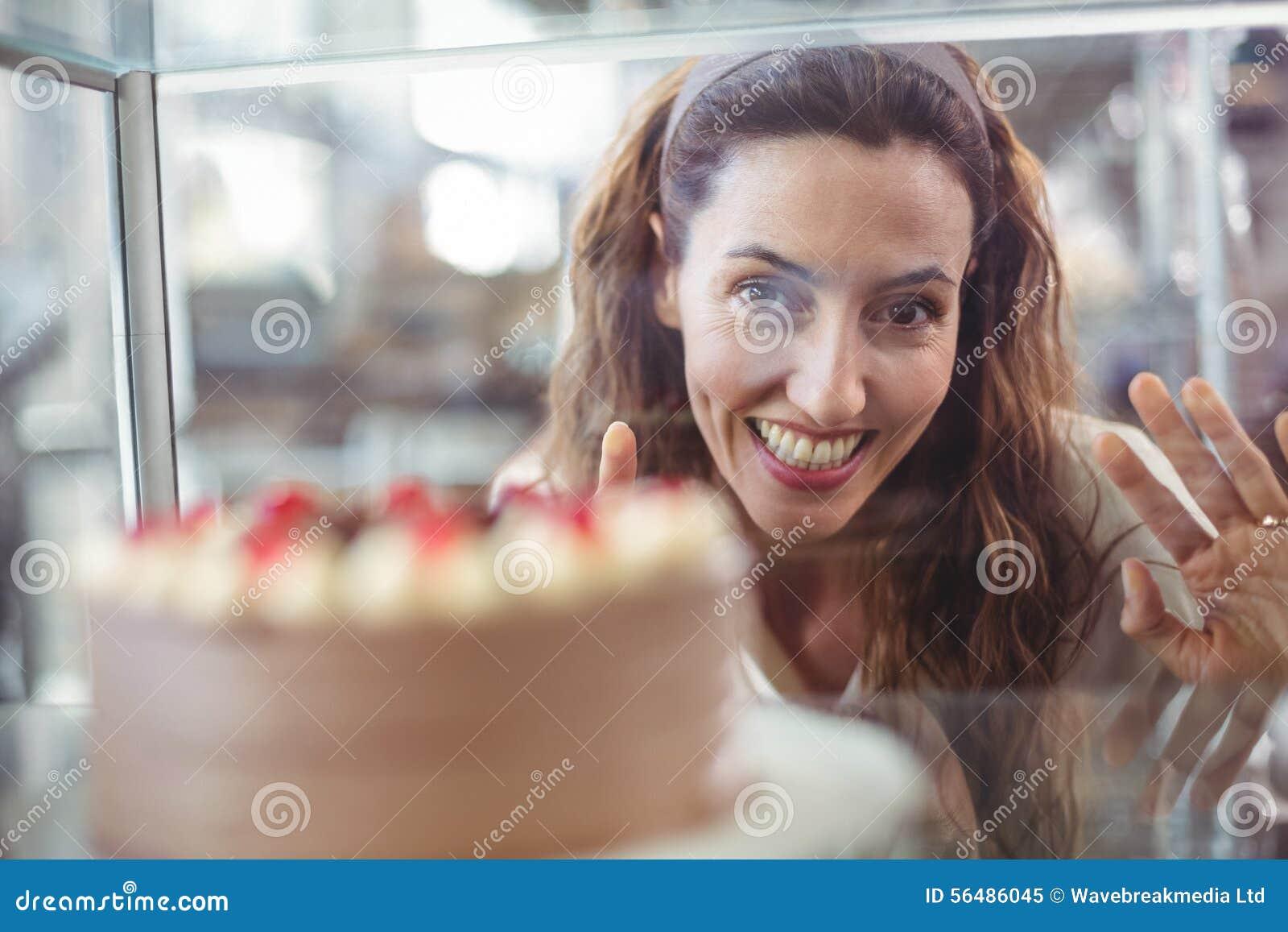 Jolie brune regardant le gâteau de chocolat par le verre