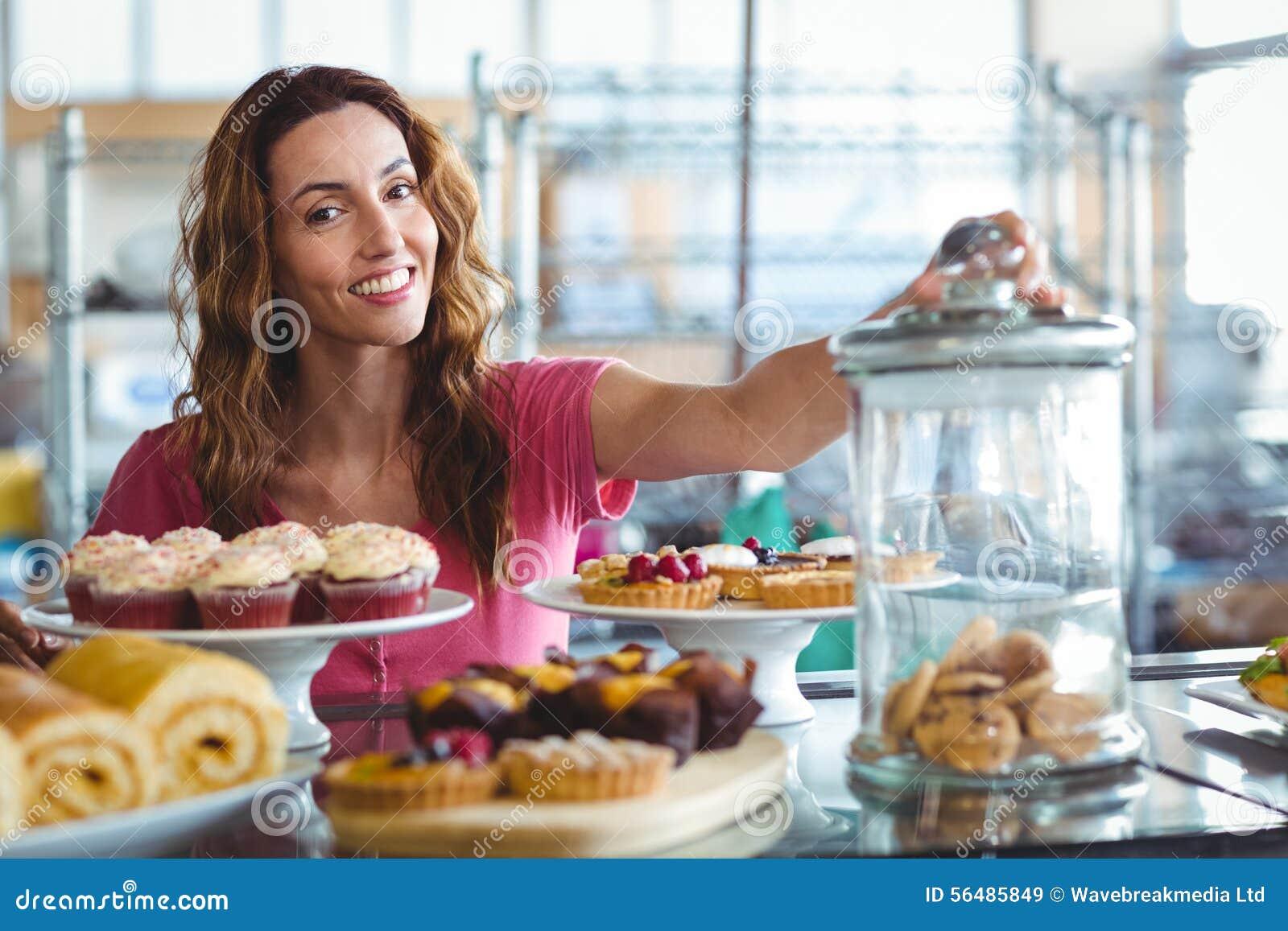 Jolie brune souriant à l appareil-photo derrière des plats des pâtisseries