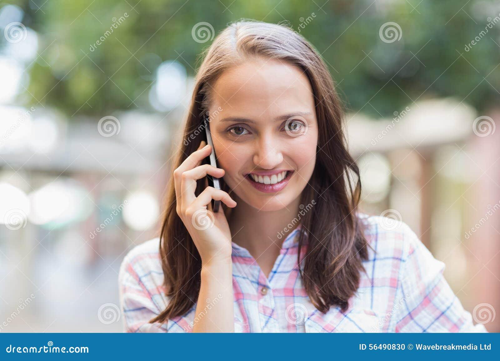 Jolie brune souriant à l appareil-photo et ayant un appel téléphonique
