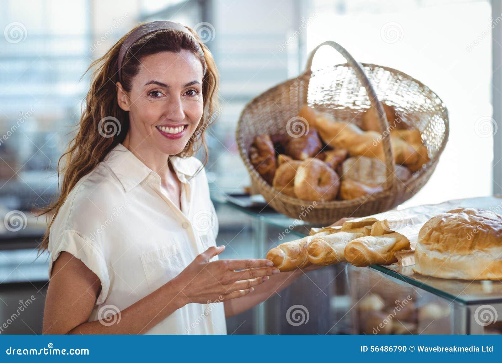 Jolie brune souriant à l appareil-photo et tenant la miche de pain