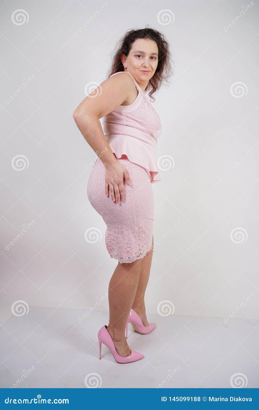 Jolie danse positive potelée de fille dans la robe à la mode rose sur le fond blanc de studio