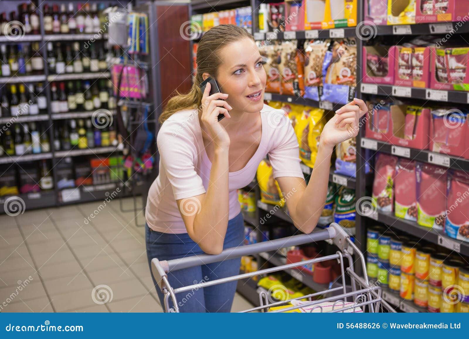 Jolie femme ayant l appel téléphonique et poussant le chariot
