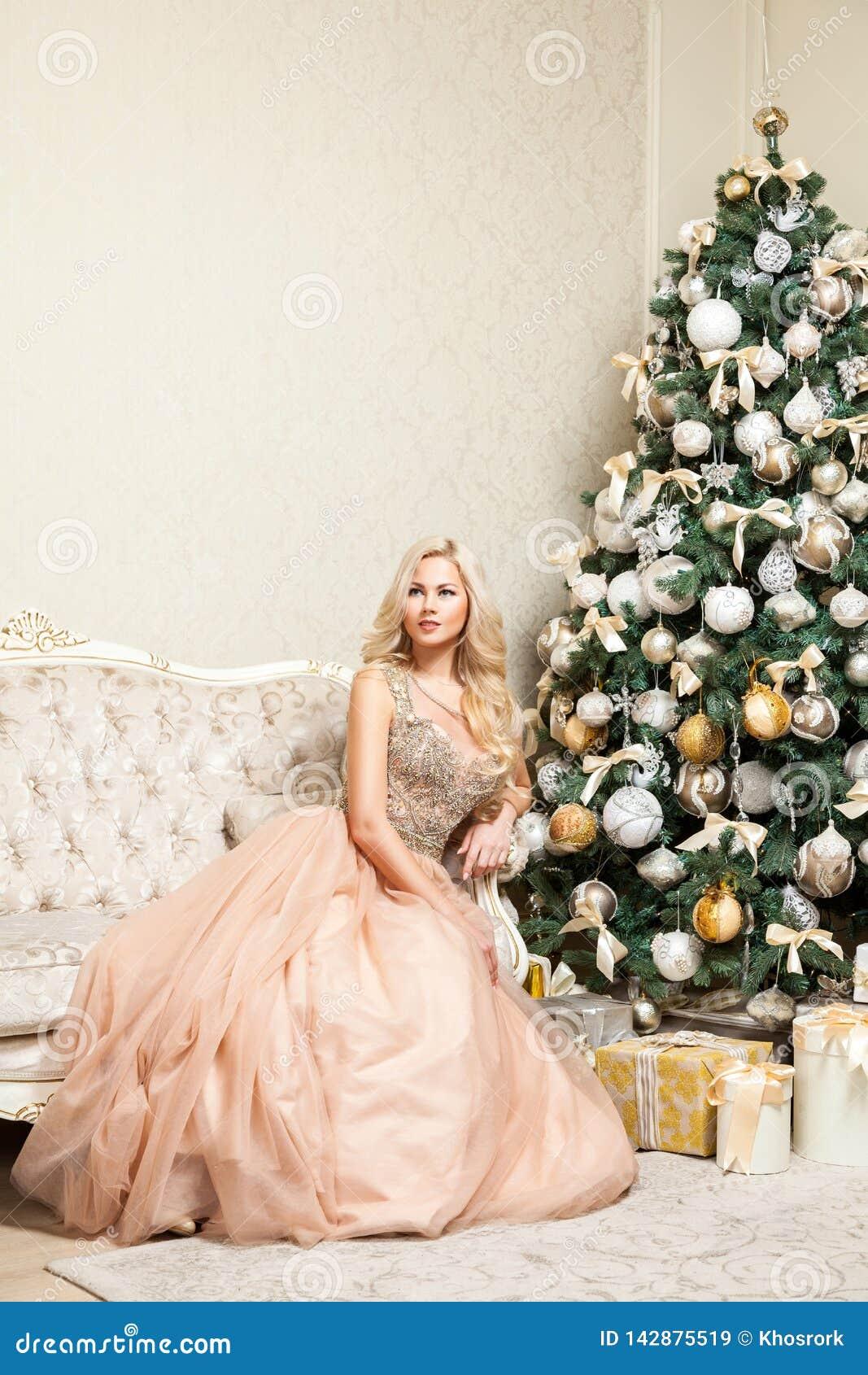 Jolie femme blonde dans la robe égalisante élégante gonflée de belles vacances avec presque la pose se reposante de maquillage et
