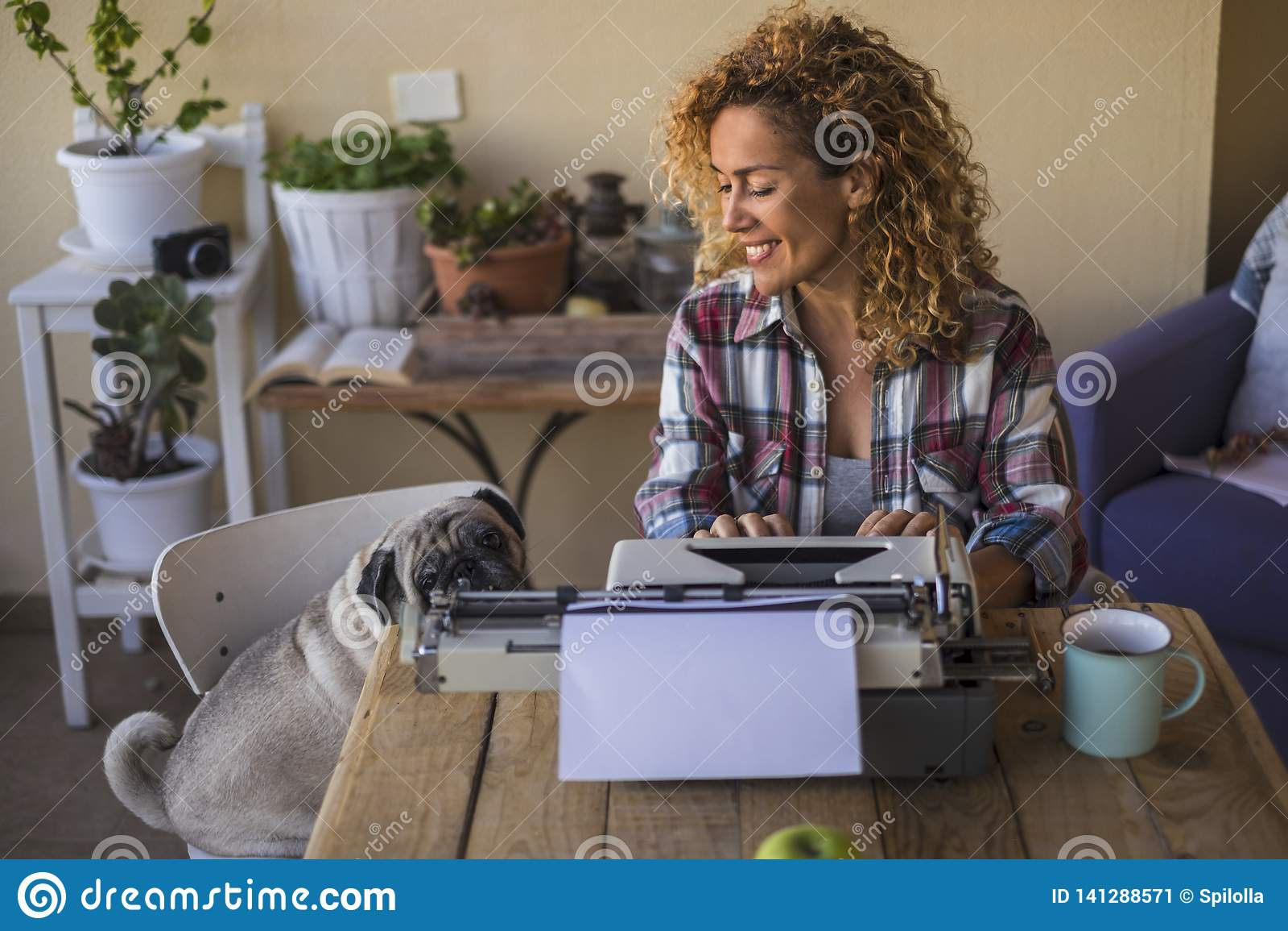 Jolie femme caucasienne de Moyen Âge utiliser une vieille machine à écrire pour écrire un blog ou un livre extérieur près de son