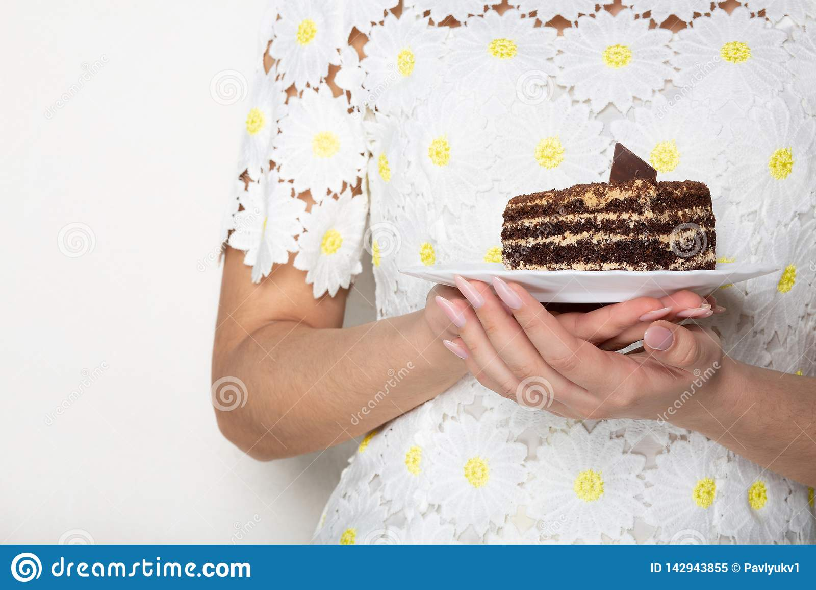 Jolie femme dans la robe à la mode tenant un plat avec le gâteau de chocolat savoureux L espace pour le texte