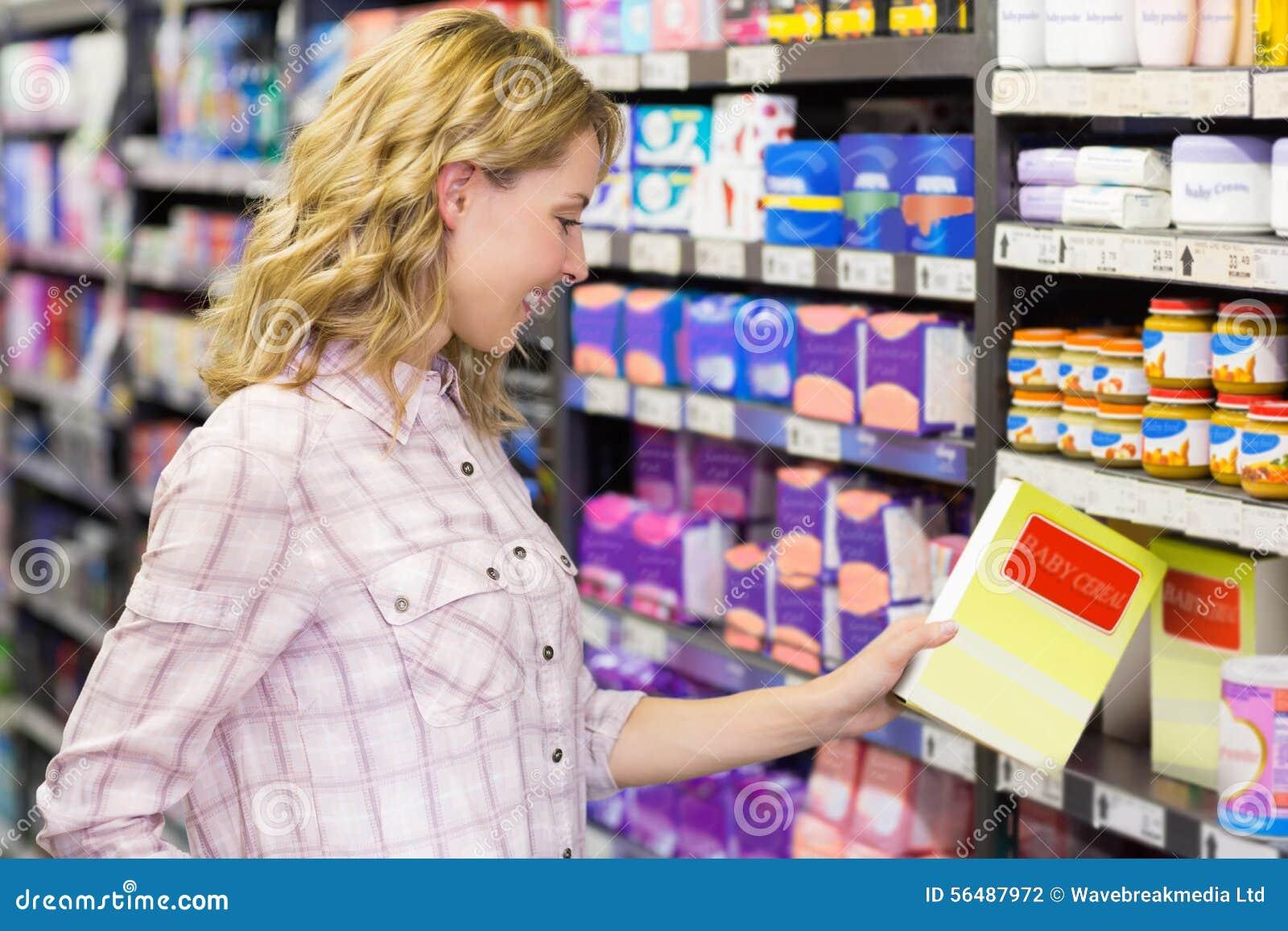 Jolie femme de sourire regardant un produit