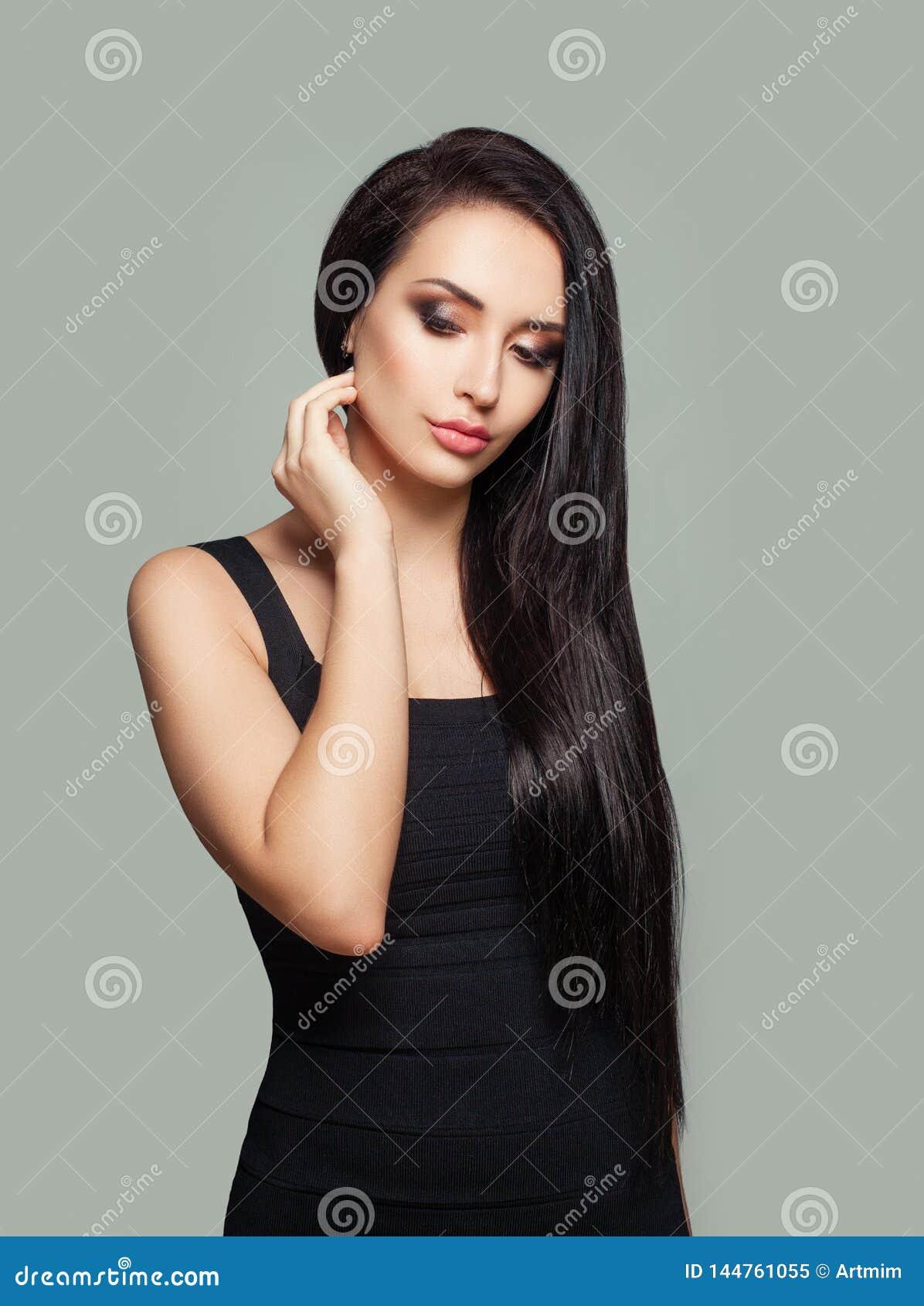 Jolie femme modèle avec de longs cheveux droits et maquillage portant la robe noire posant sur le fond gris de mur