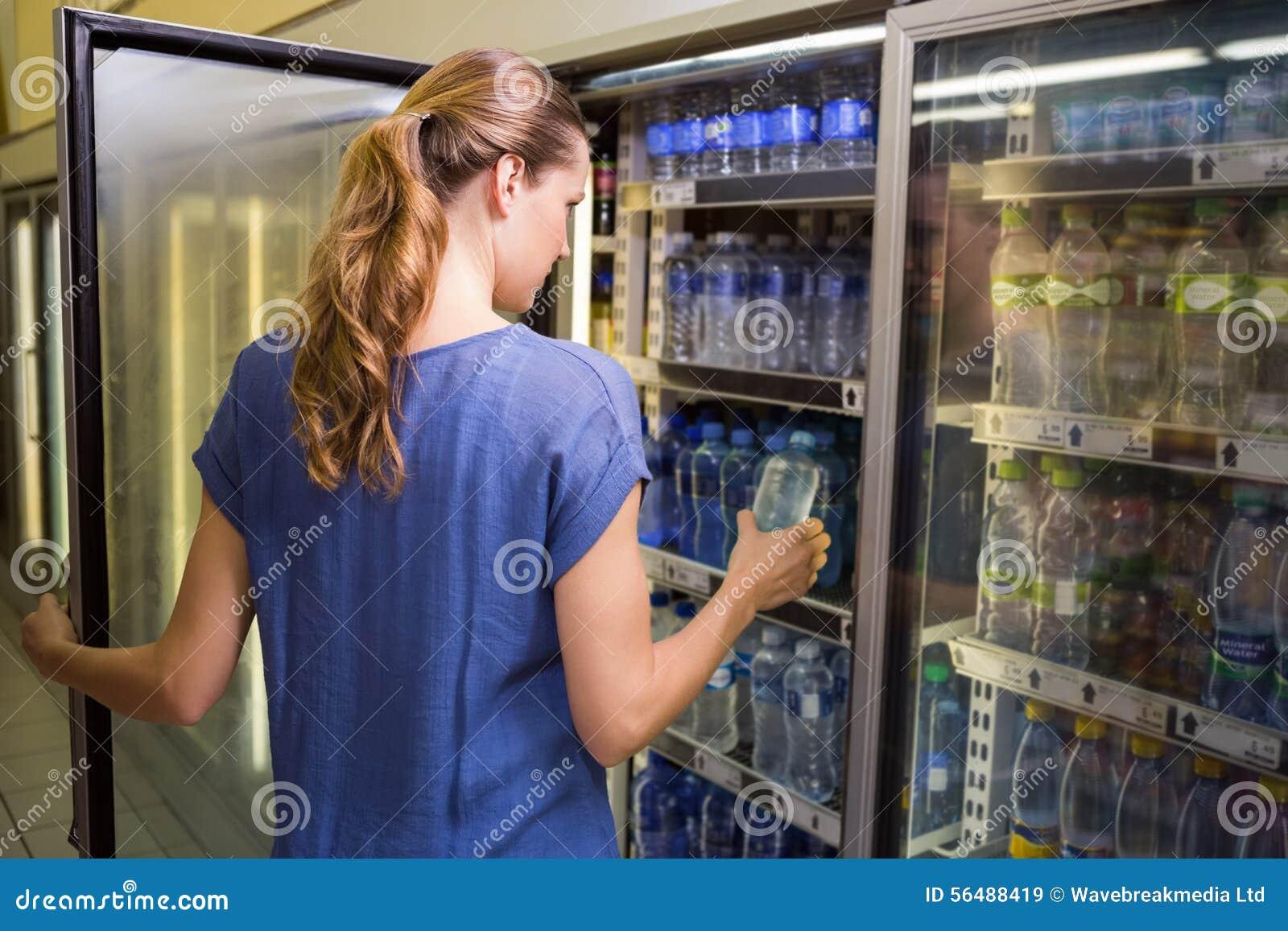 Jolie femme prenant la bouteille de l eau dans le réfrigérateur
