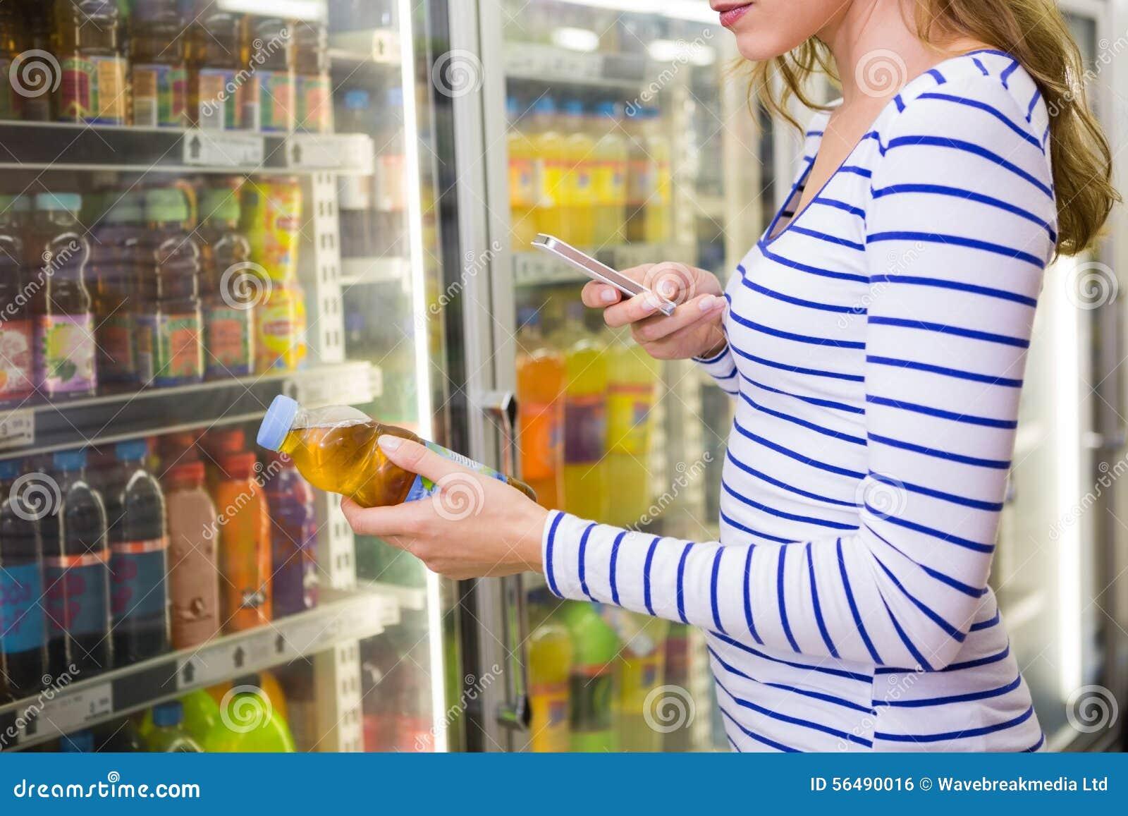 Jolie femme prenant la photo de la bouteille