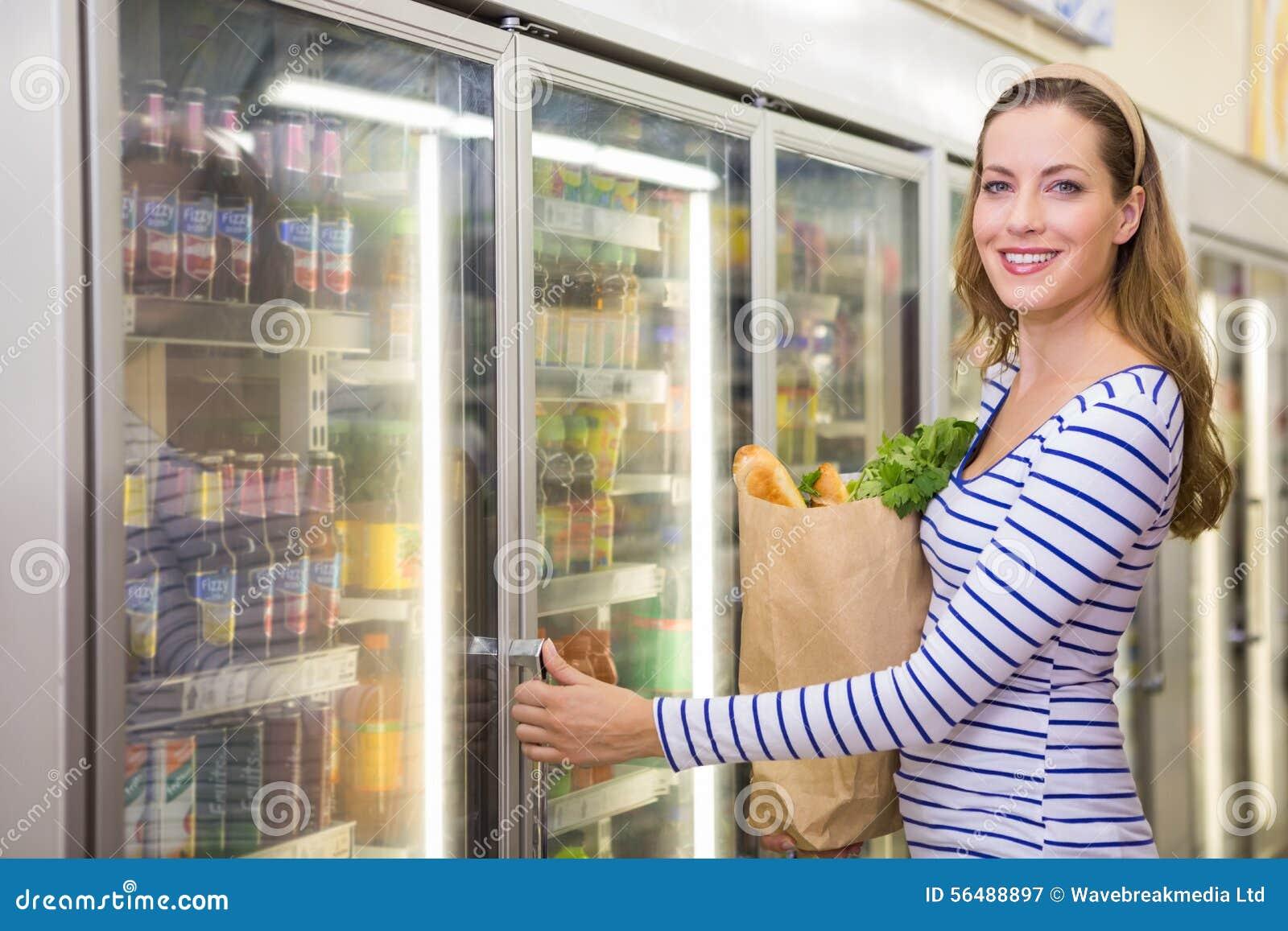 Jolie femme prenant le produit sur le réfrigérateur
