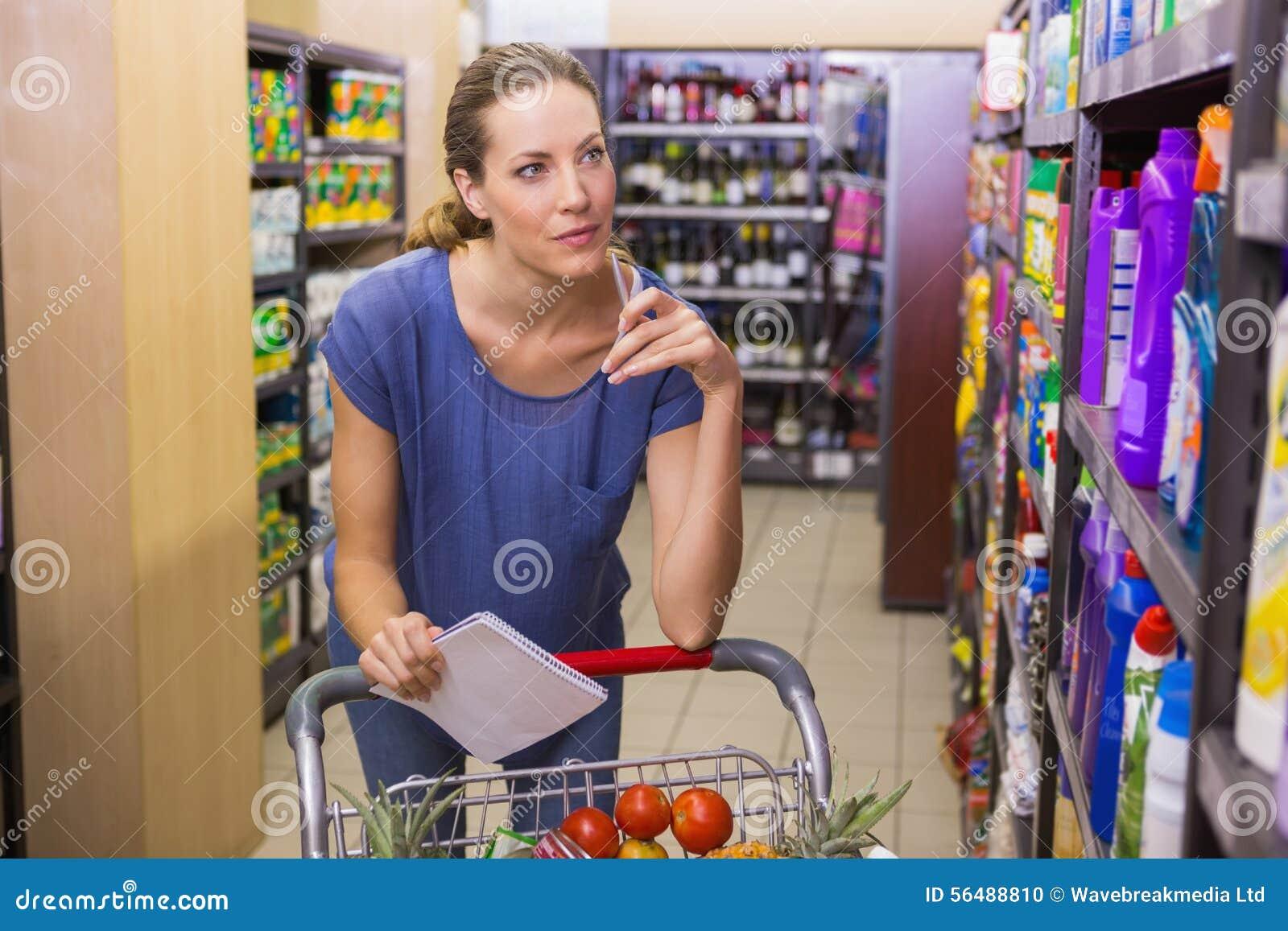 Jolie femme regardant le produit sur l étagère et tenant la liste d épicerie