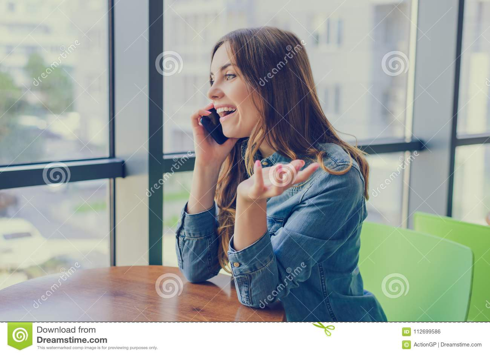 Jolie femme riante enthousiaste s asseyant dans un café, elle parle au téléphone et bavarde avec son meilleur ami Émotion exprima
