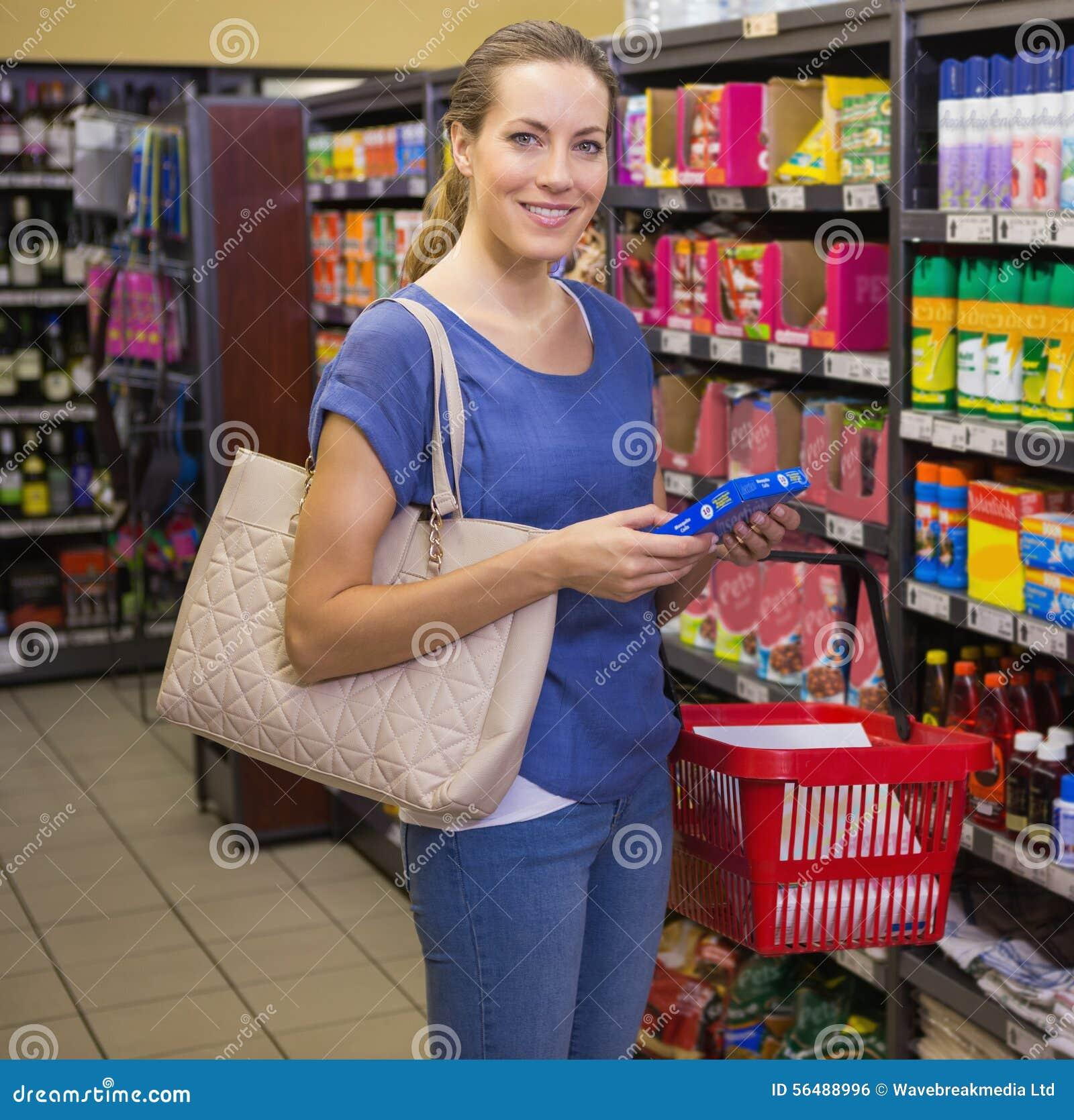 Jolie femme tenant le produit et regardant l appareil-photo