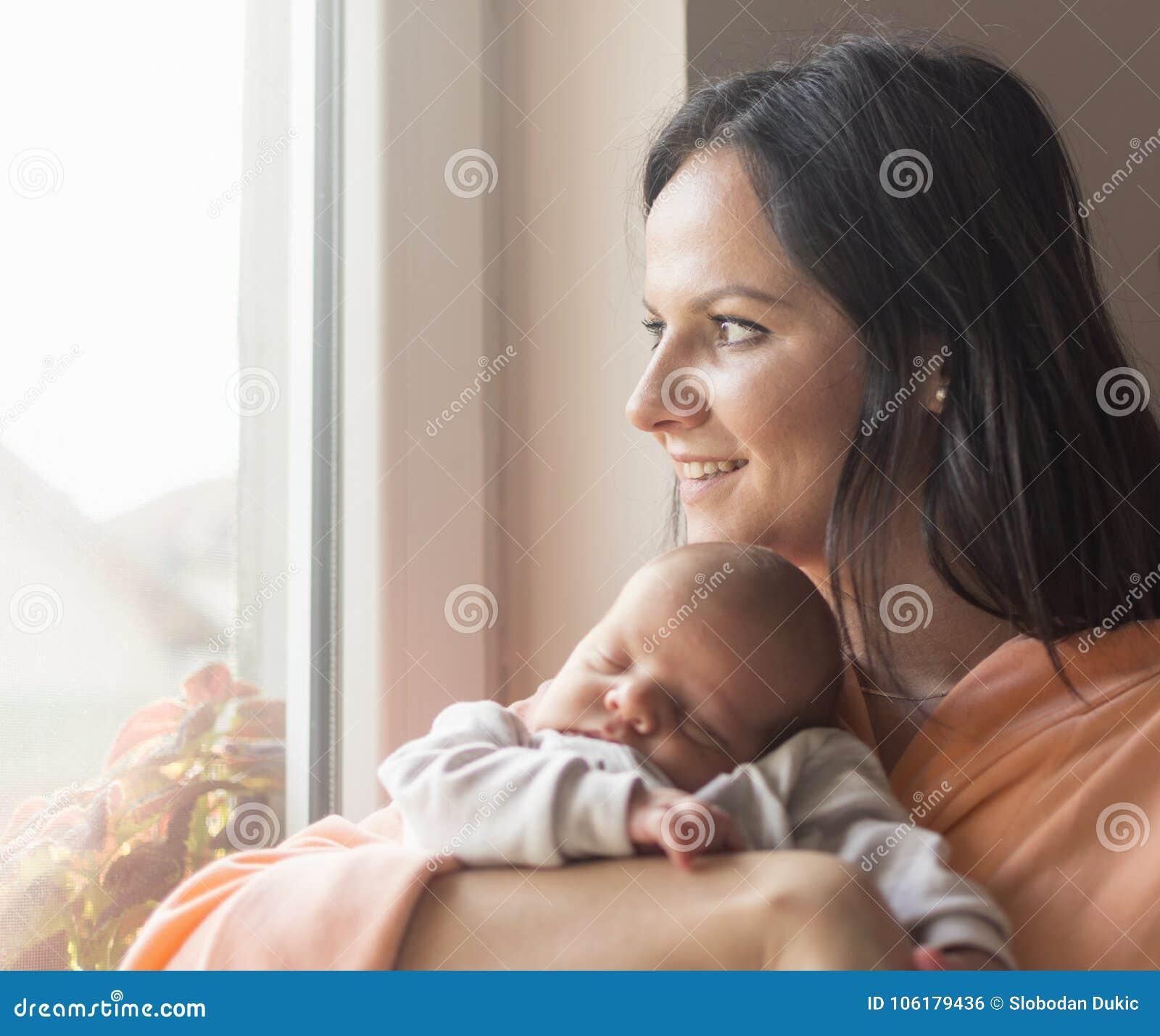 Jolie femme tenant un bébé nouveau-né dans des ses bras