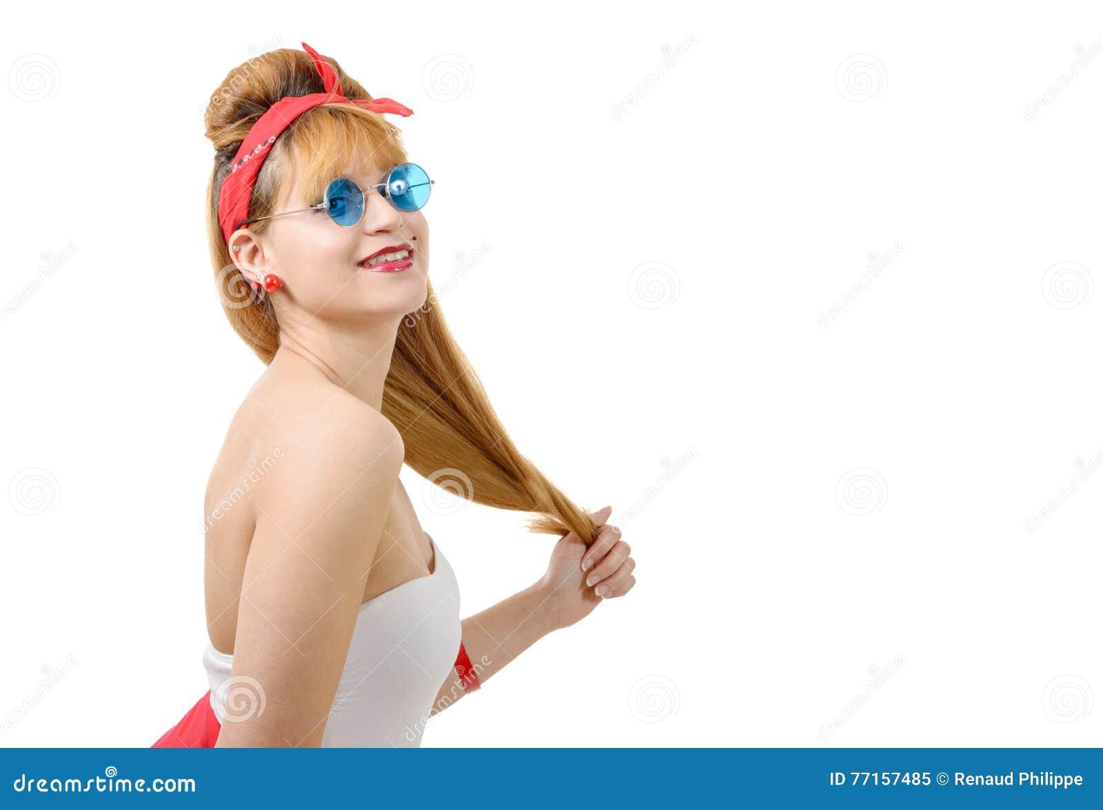 Jolie fille dans le rétro style avec les lunettes de soleil bleues sur le blanc