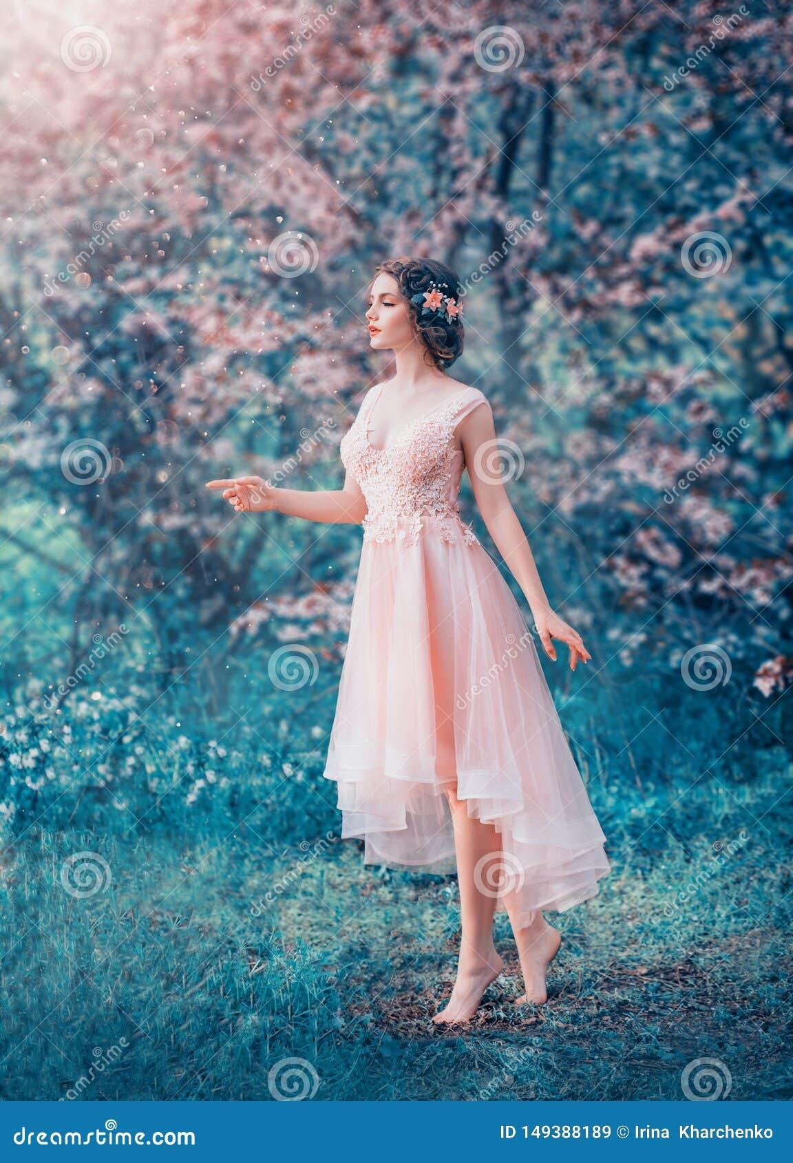 Jolie fille mince avec les cheveux fonc?s tress?s dans une robe ?l?gante sensible de p?che, une princesse de conte de f?es dans u