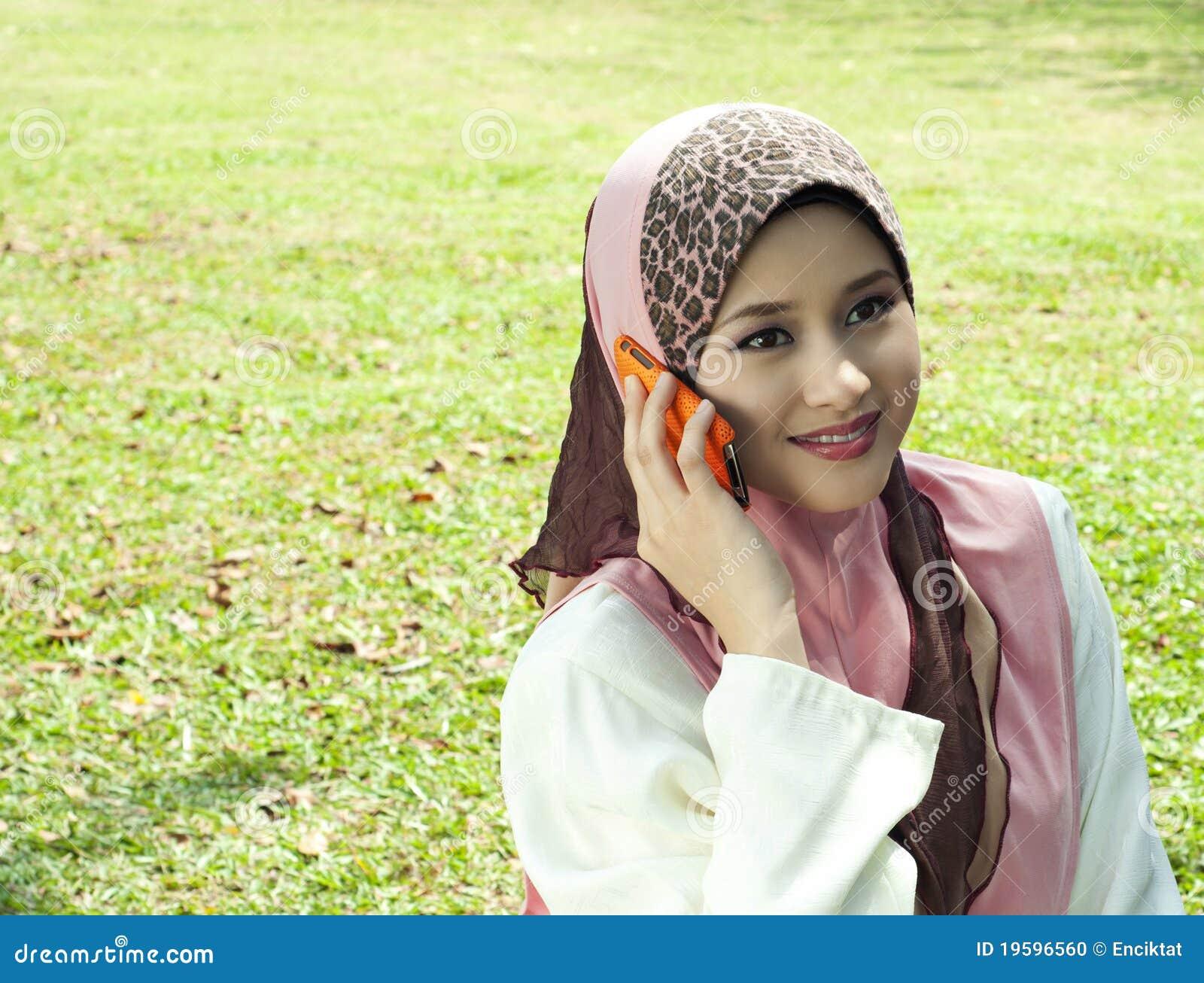 Jolie fille musulmane avec un téléphone au jardin