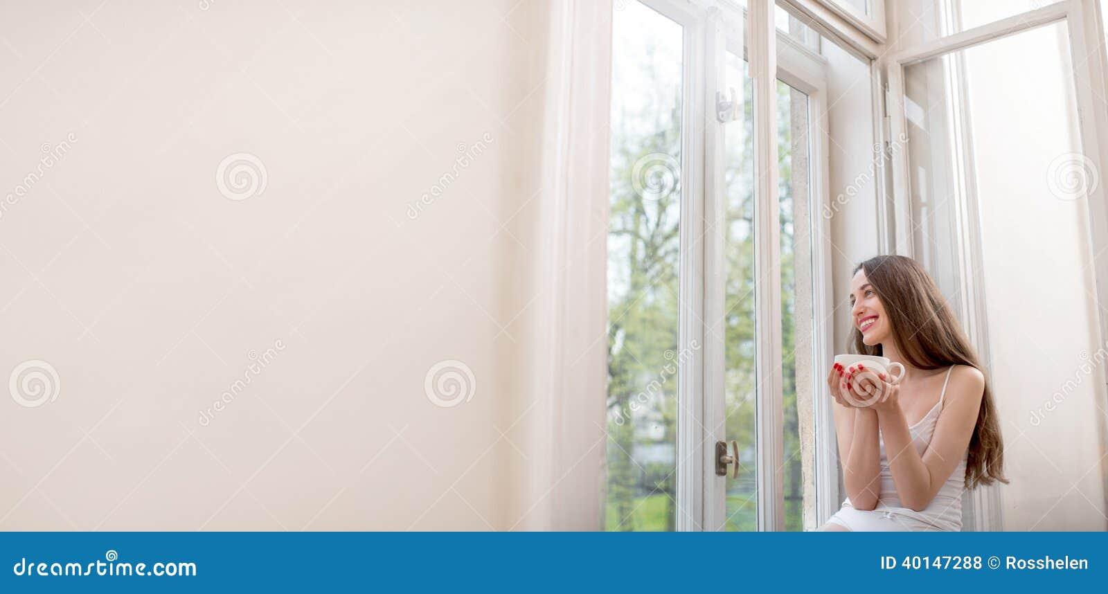 Jolie fille s 39 asseyant pr s de la fen tre et regardant la for Fille a la fenetre