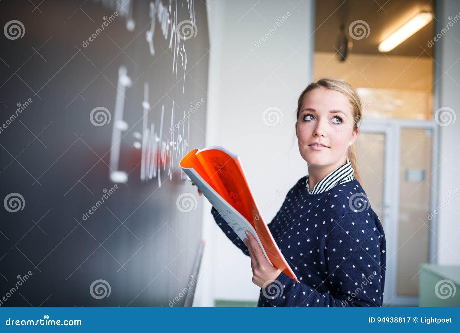 Jolie, jeune écriture d étudiant universitaire sur le tableau/blackboa