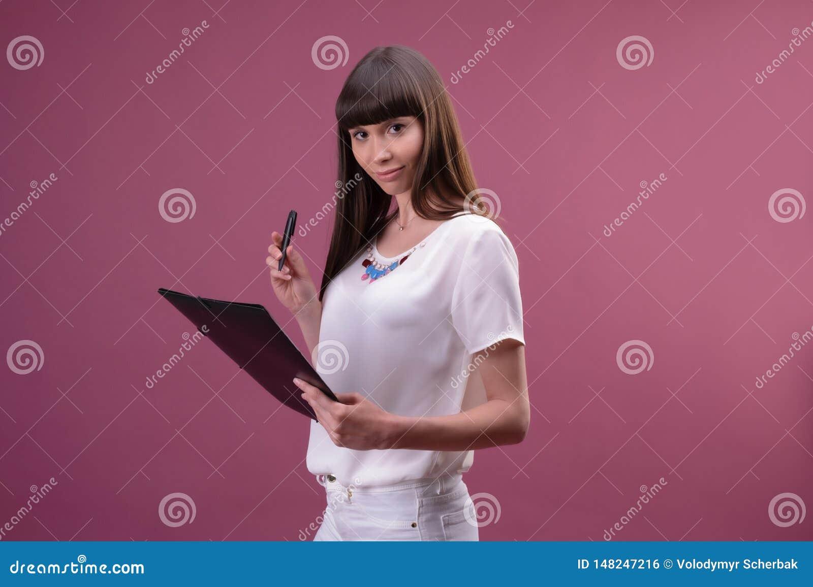 Jolie jeune belle position de femme, ?criture, notes de prise, tenant l organisateur de manuel ? disposition et le stylo