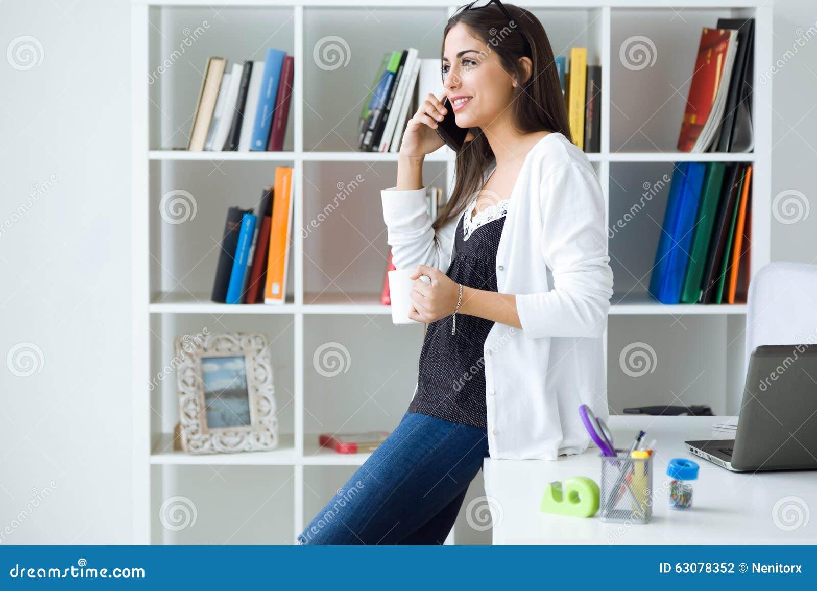 Download Jolie Jeune Femme à L'aide De Son Téléphone Portable Dans Le Bureau Photo stock - Image du verticale, personne: 63078352
