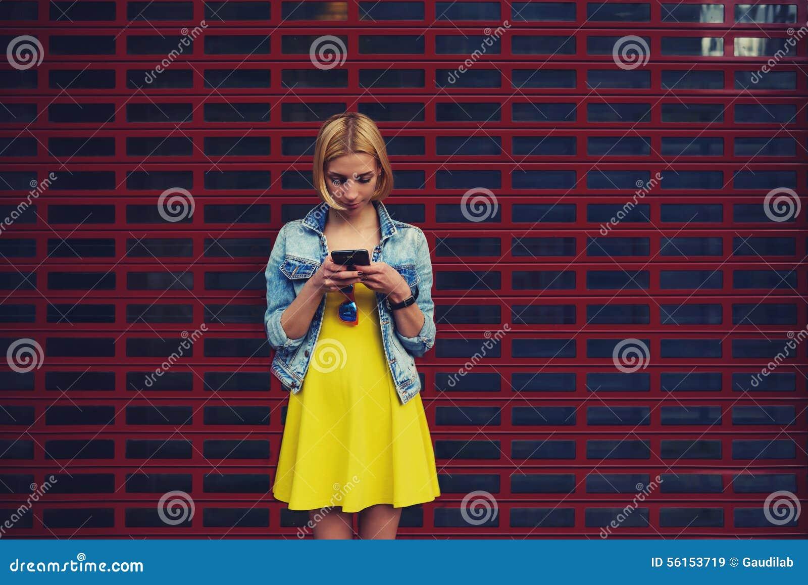 Jolie jeune femme causant sur son smartphone sur le fond lumineux de l espace vide de copie pour votre contenu ou message textuel