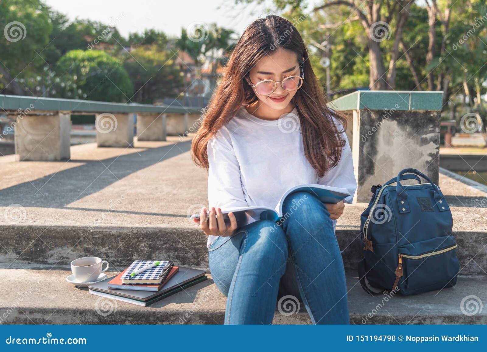 Jolie jeune femme décontractée lisant un livre à la pelouse avec briller du soleil