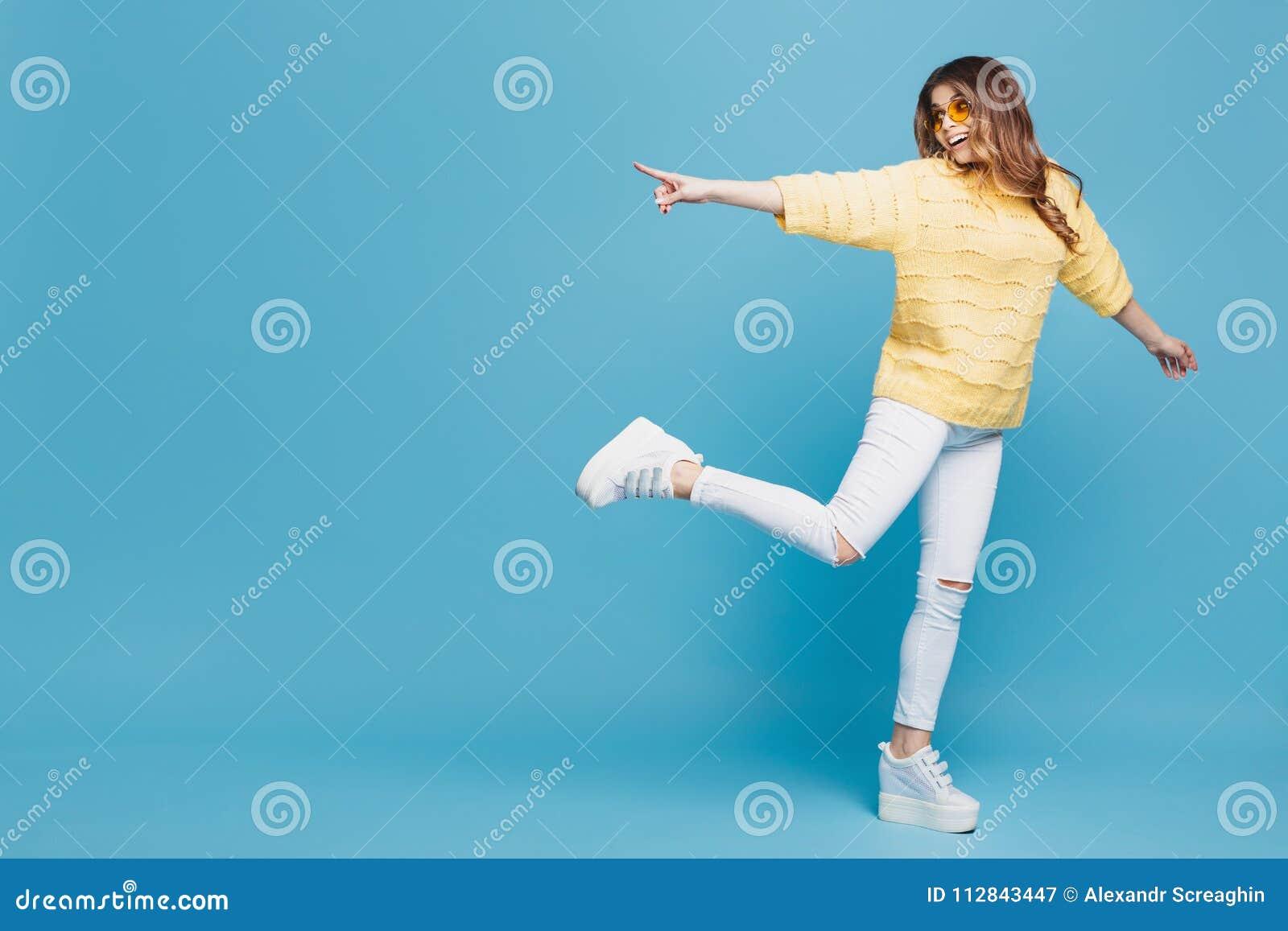 Jolie jeune femme dans le chandail jaune posant sur le fond bleu Femme attirante indiquant des doigts la gauche avec