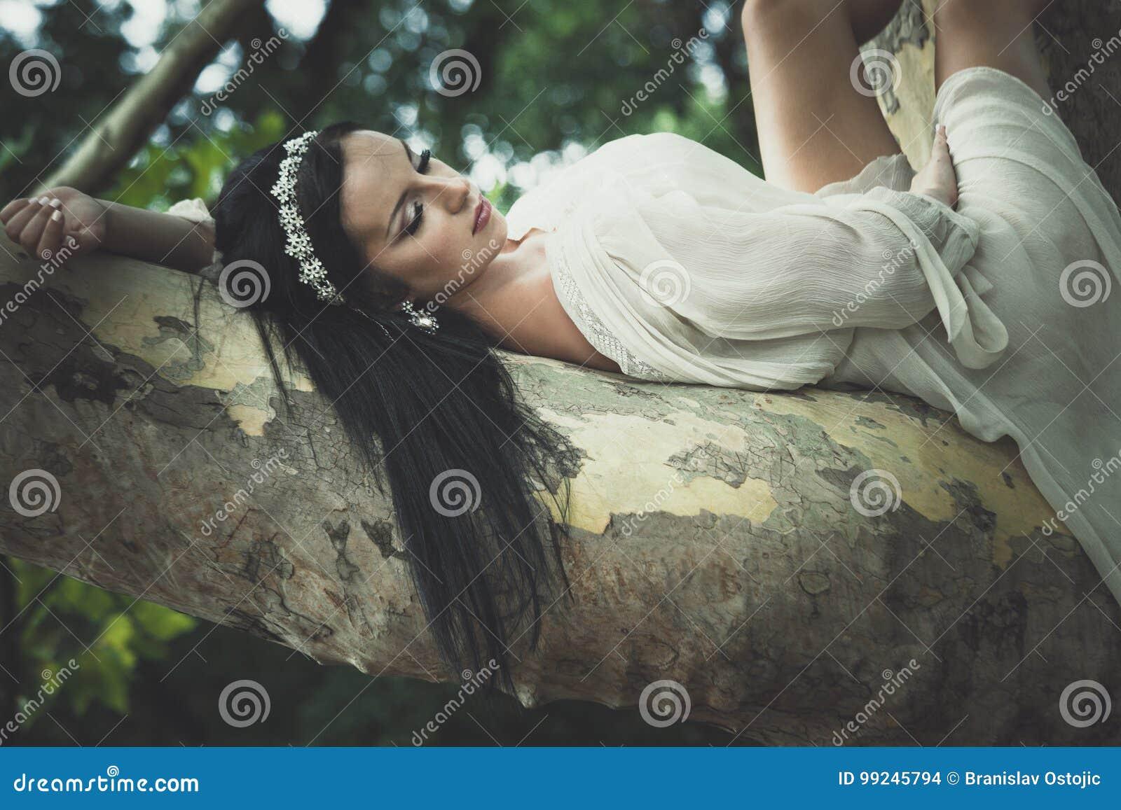 Jolie jeune femme dans le mensonge romantique de robe sur l arbre en parc