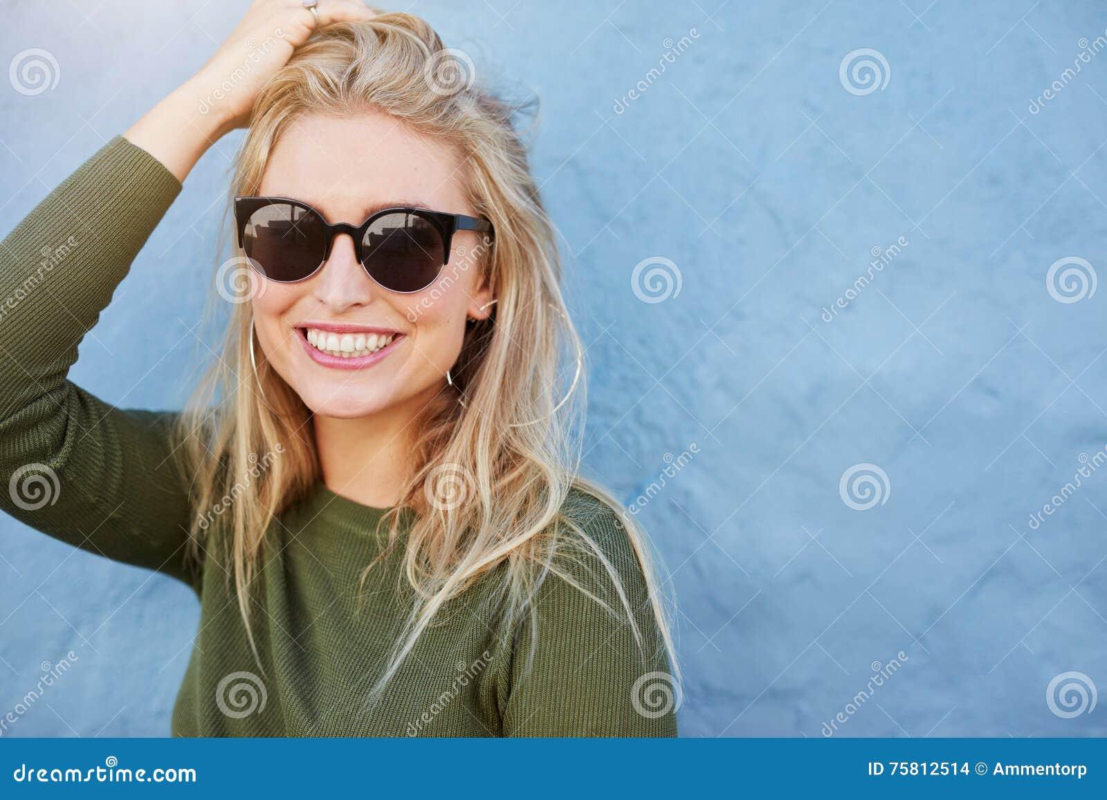 Jolie jeune femme dans le sourire de lunettes de soleil