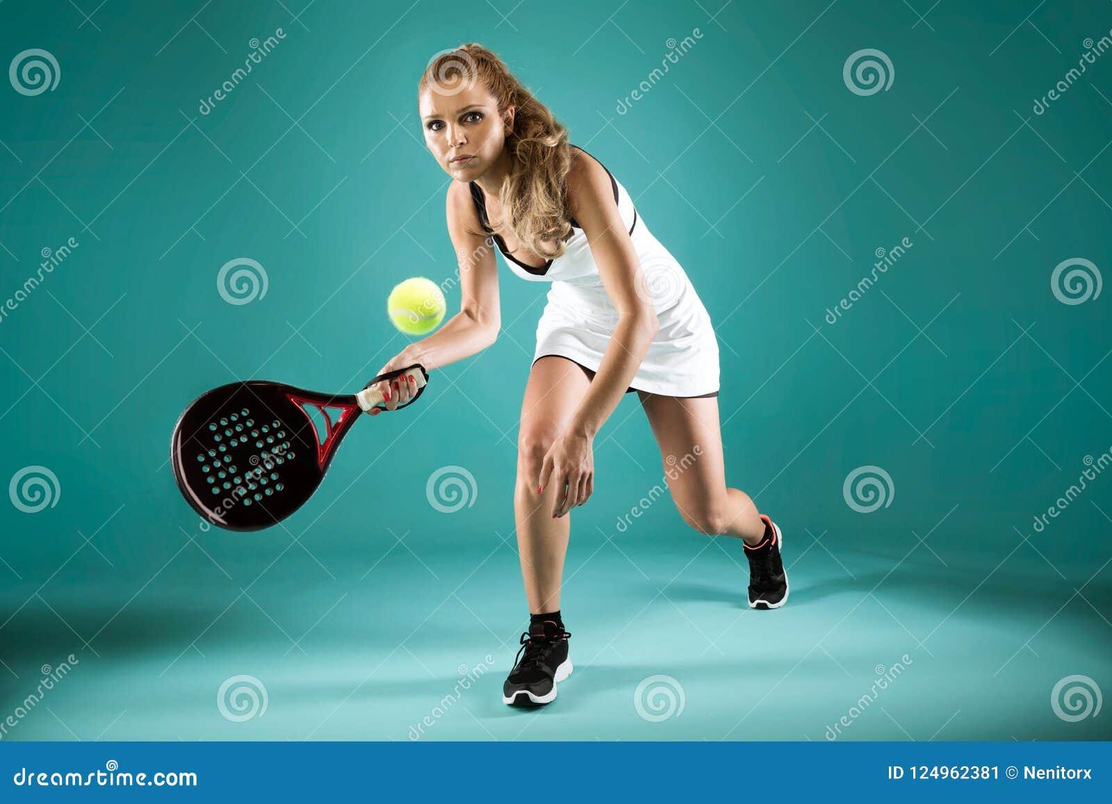 Jolie jeune femme jouant le padel d intérieur au-dessus du backgrou vert-bleu