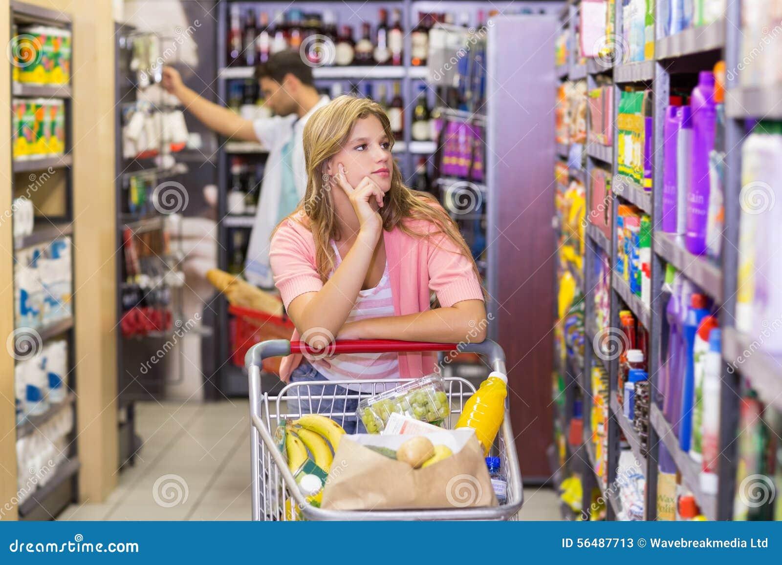 Jolie jeune femme regardant l étagère