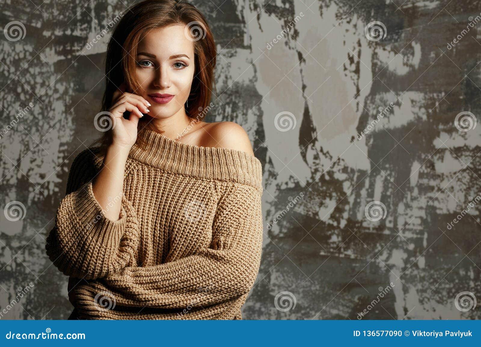 Jolie jeune femme utilisant le chandail tricoté avec l épaule nue, posant avec des ombres L espace vide