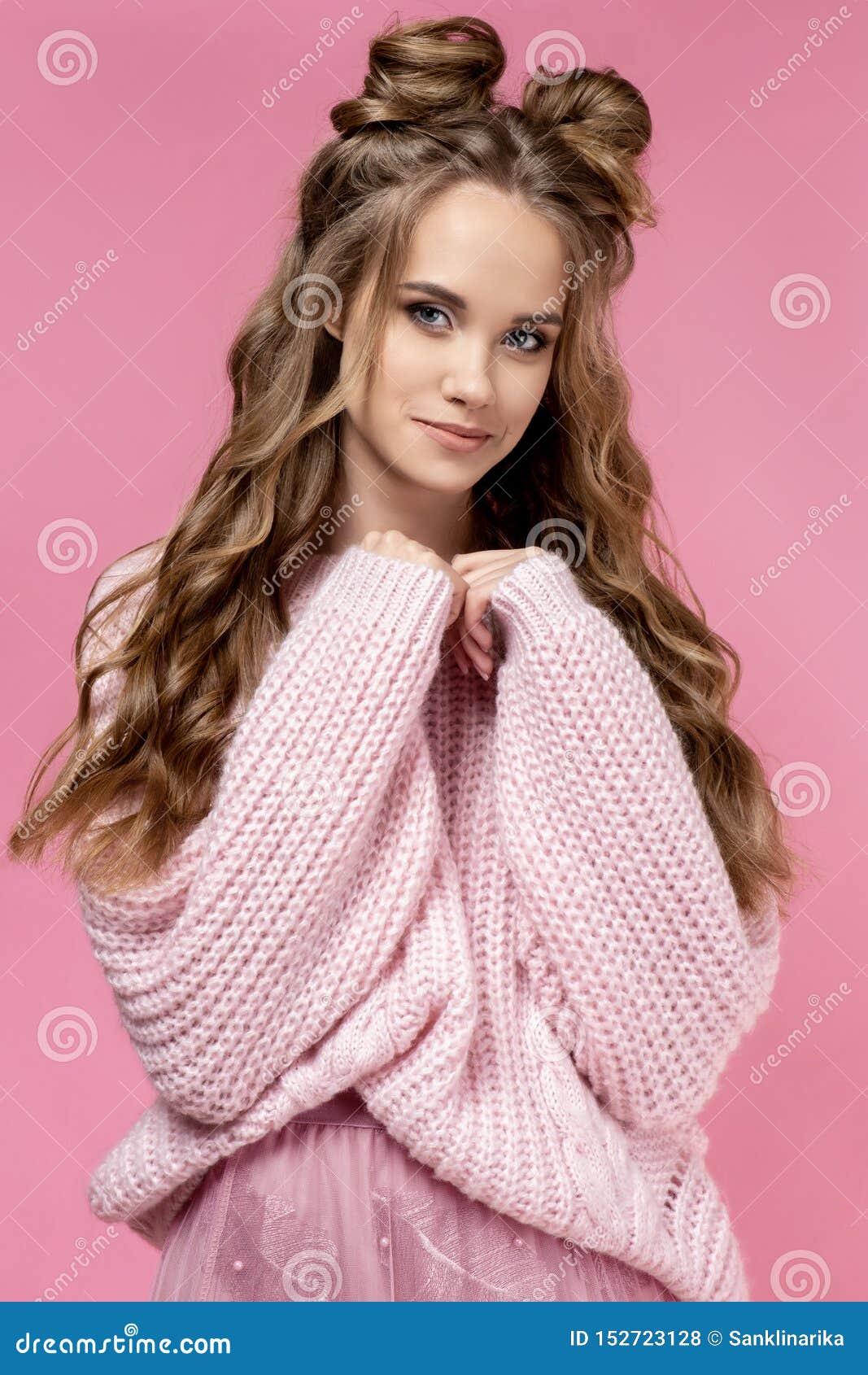 Jolie jeune fille dans un chandail rose sur un fond rose avec une coupe de cheveux et de longs cheveux bouclés