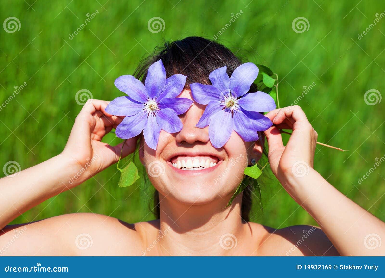 Jolie peau de femme de sourire ses yeux avec le clematis à l\u0027extérieur