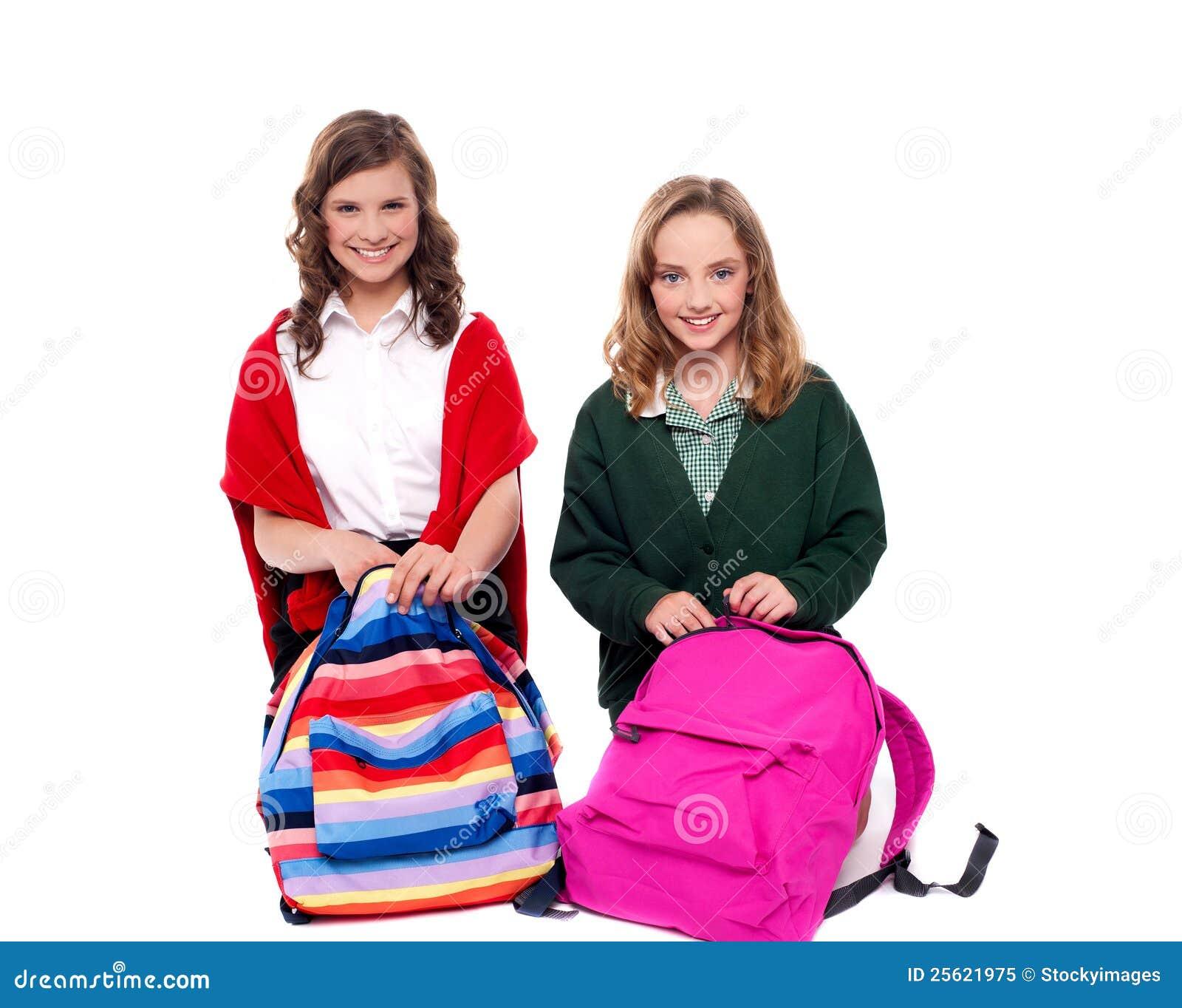 Jolies filles ouvrant le sac d'école et regardant l'appareil-photo ...