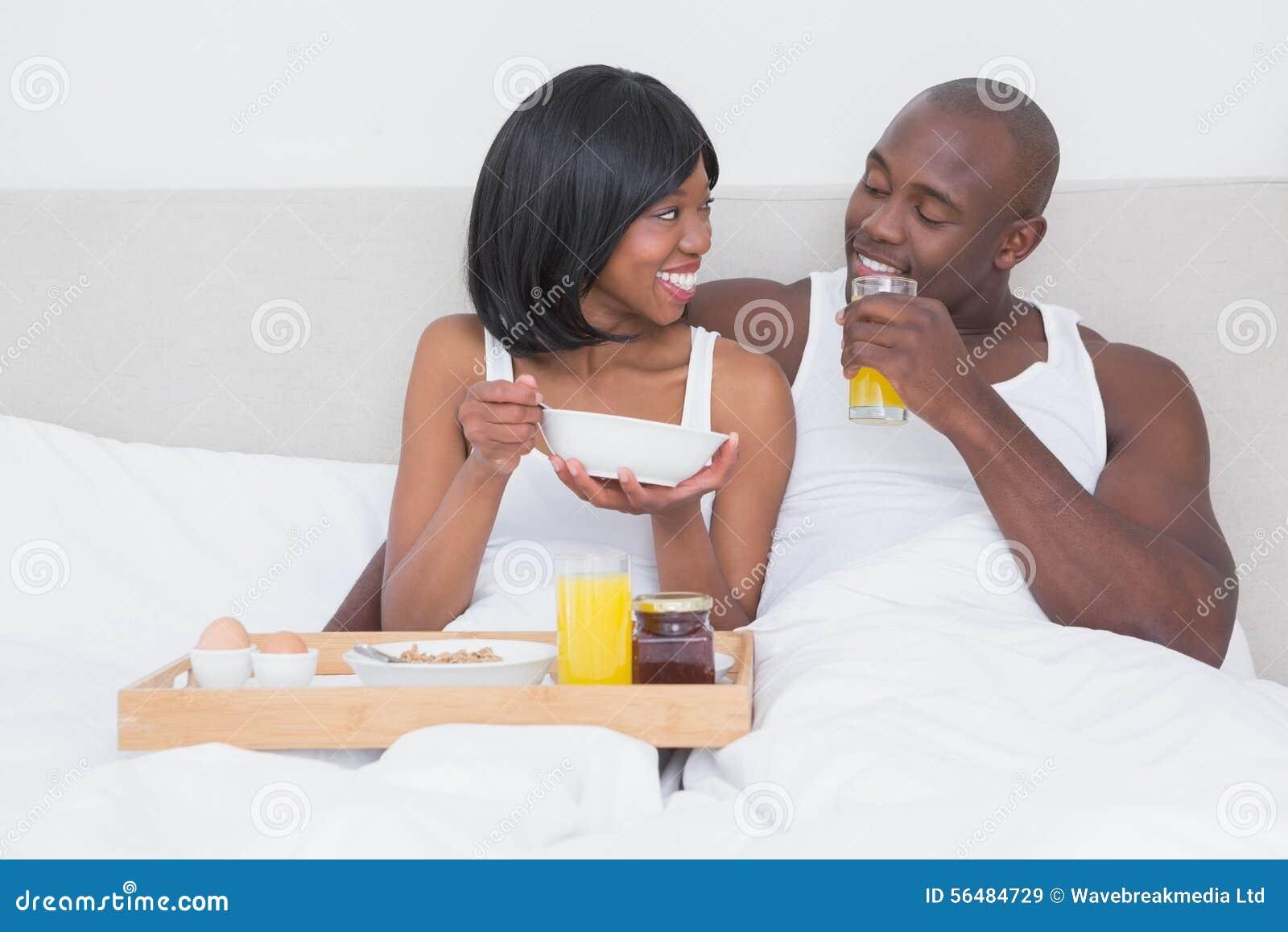Jolis couples prenant le petit déjeuner dans le lit ensemble